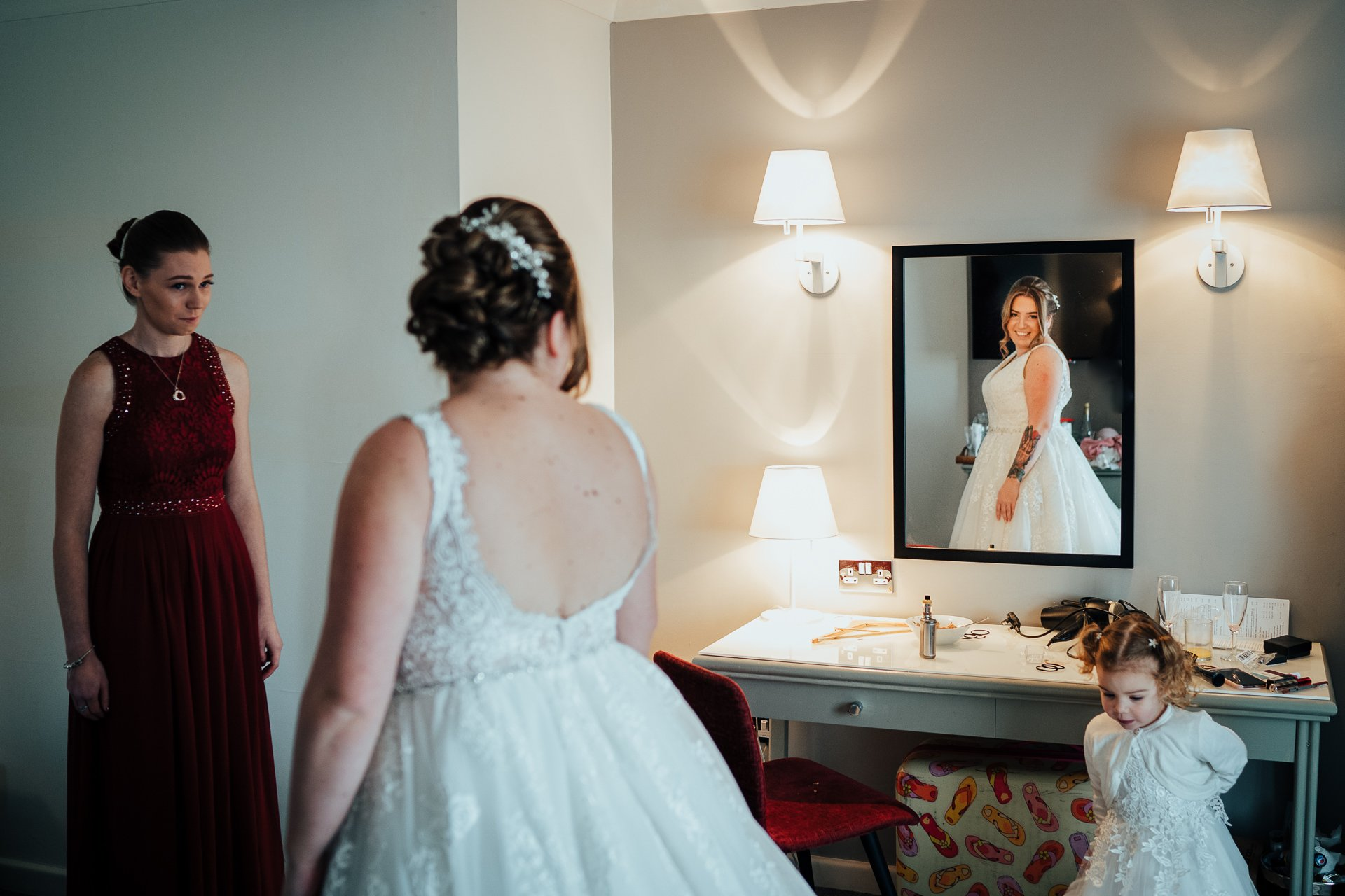 Bride looking at her reflection in the mirror in her Wedding dress