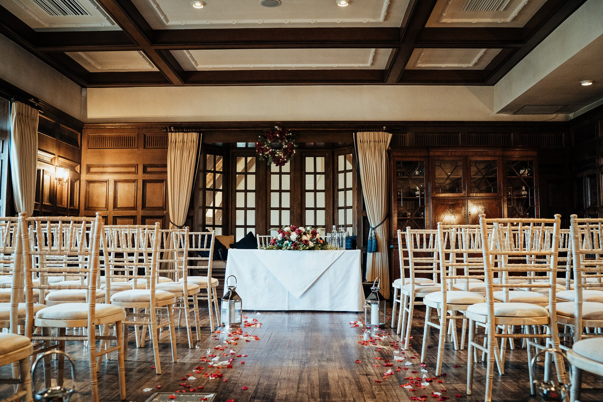 Wooden panelled wedding Ceremony room decorated with flower petals