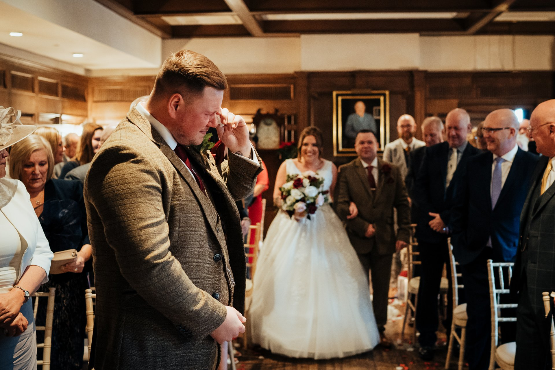 emotional Groom wiping away tears as his Bride walks down the aisle