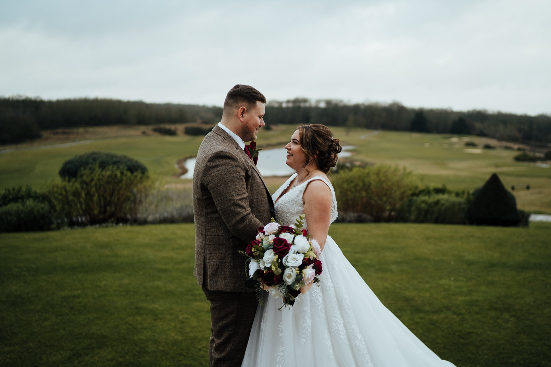 Bride and groom smiling at each other overlooking the London Golf Club Kent
