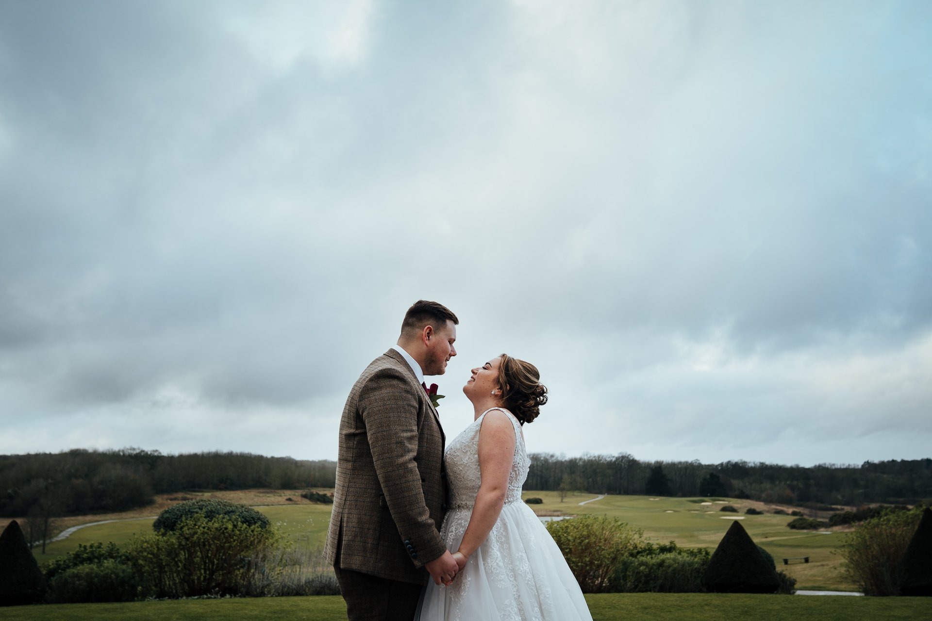 Bride and Groom embracing over looking the course at The London Golf Club, Kent