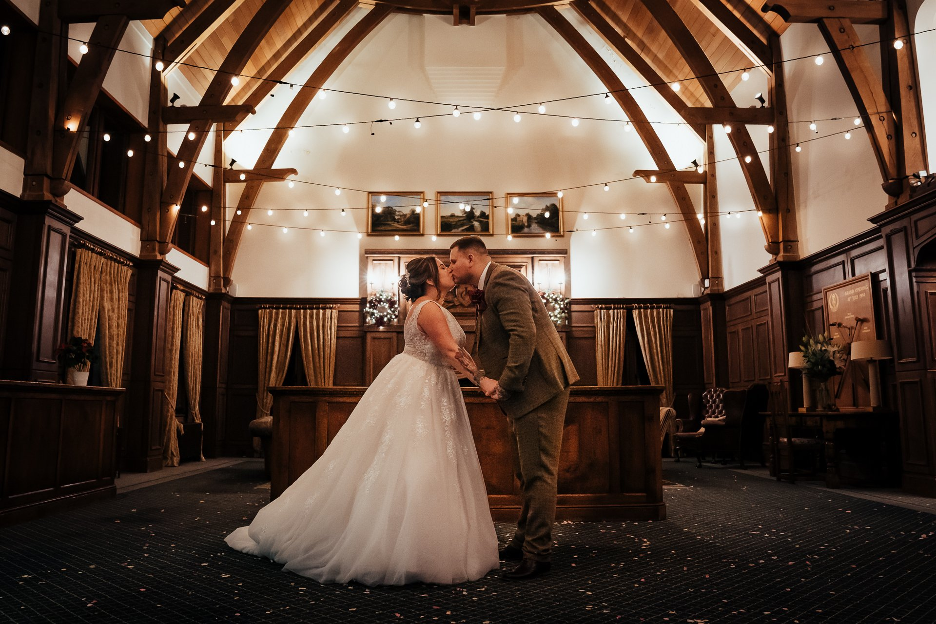 Bride and groom kissing under the lights in the Great Hall at the London Golf Club in Kent