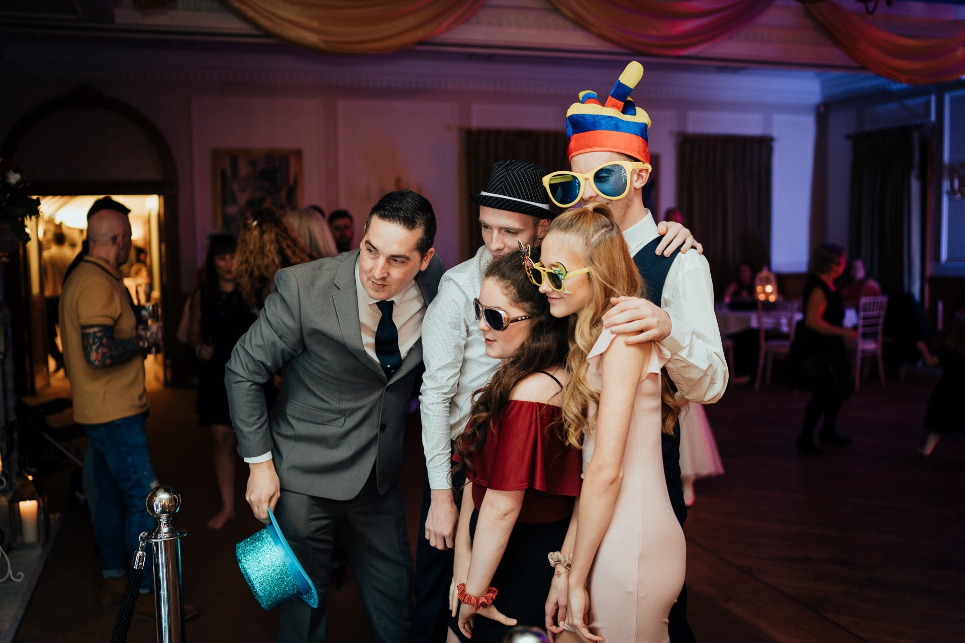 Wedding guests with accessories using a selfie mirror