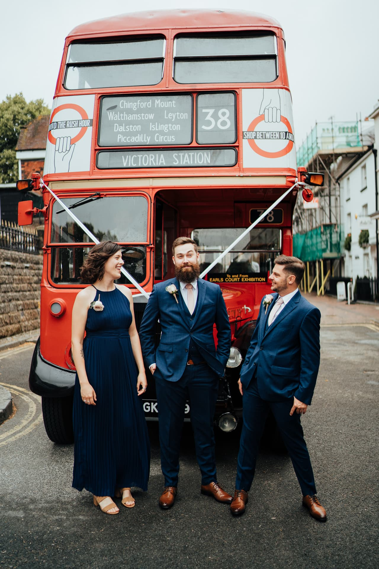 Groom and fiends in front of wedding decorated red route master bus