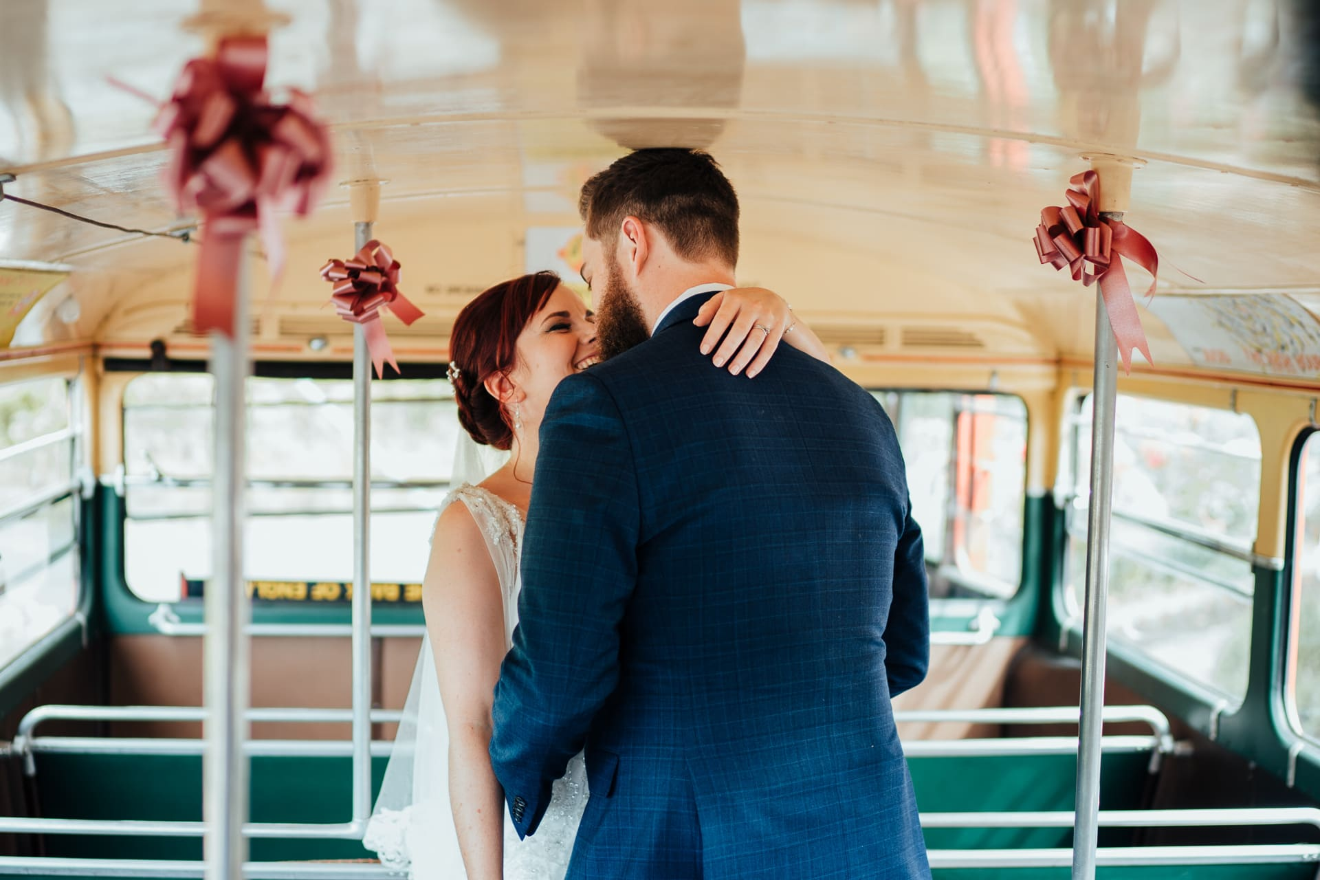 Bride and Groom kissing in the top deck of route master bus