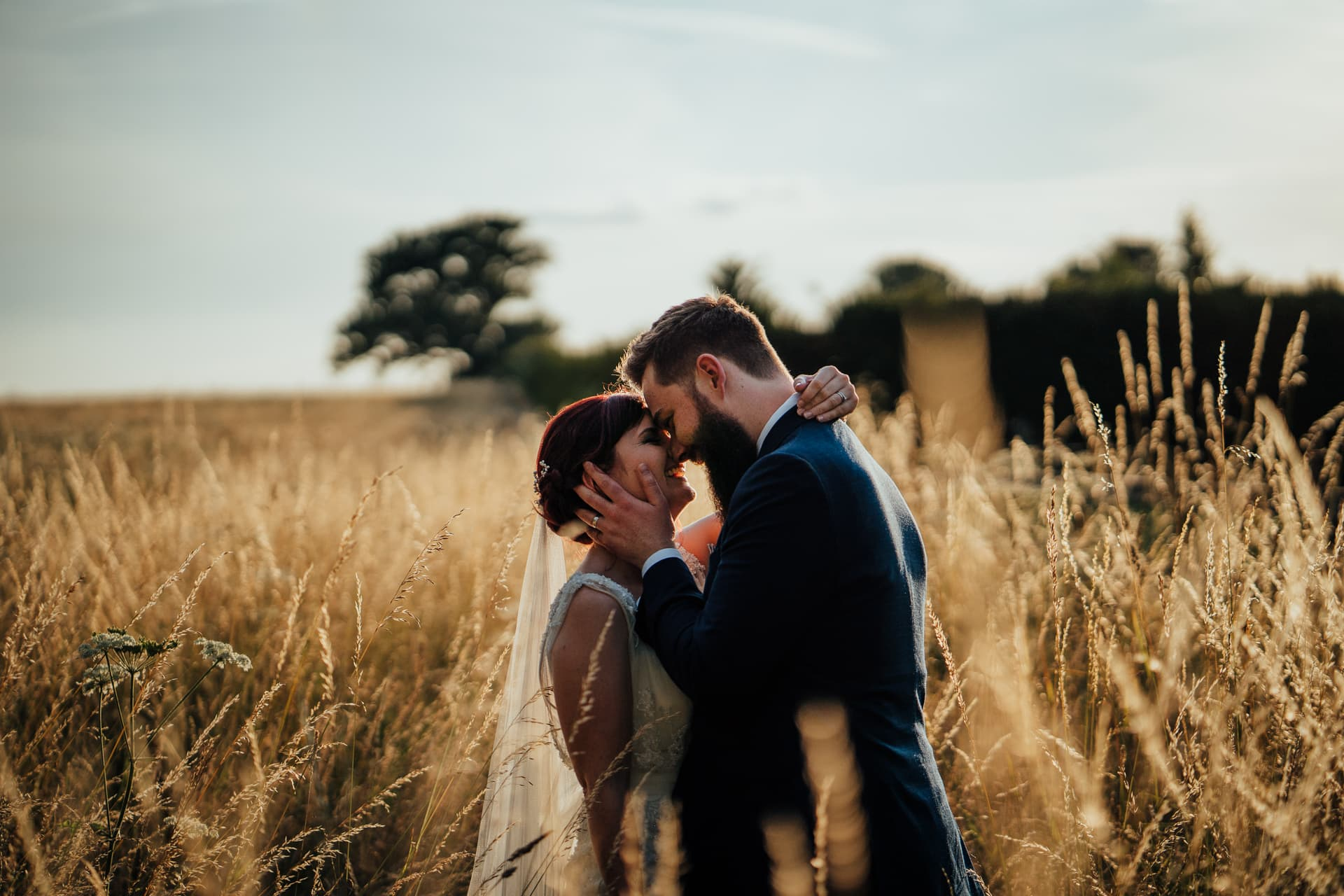 Groom holding his brides cheek in gorgeous golden hour sunset in long grass