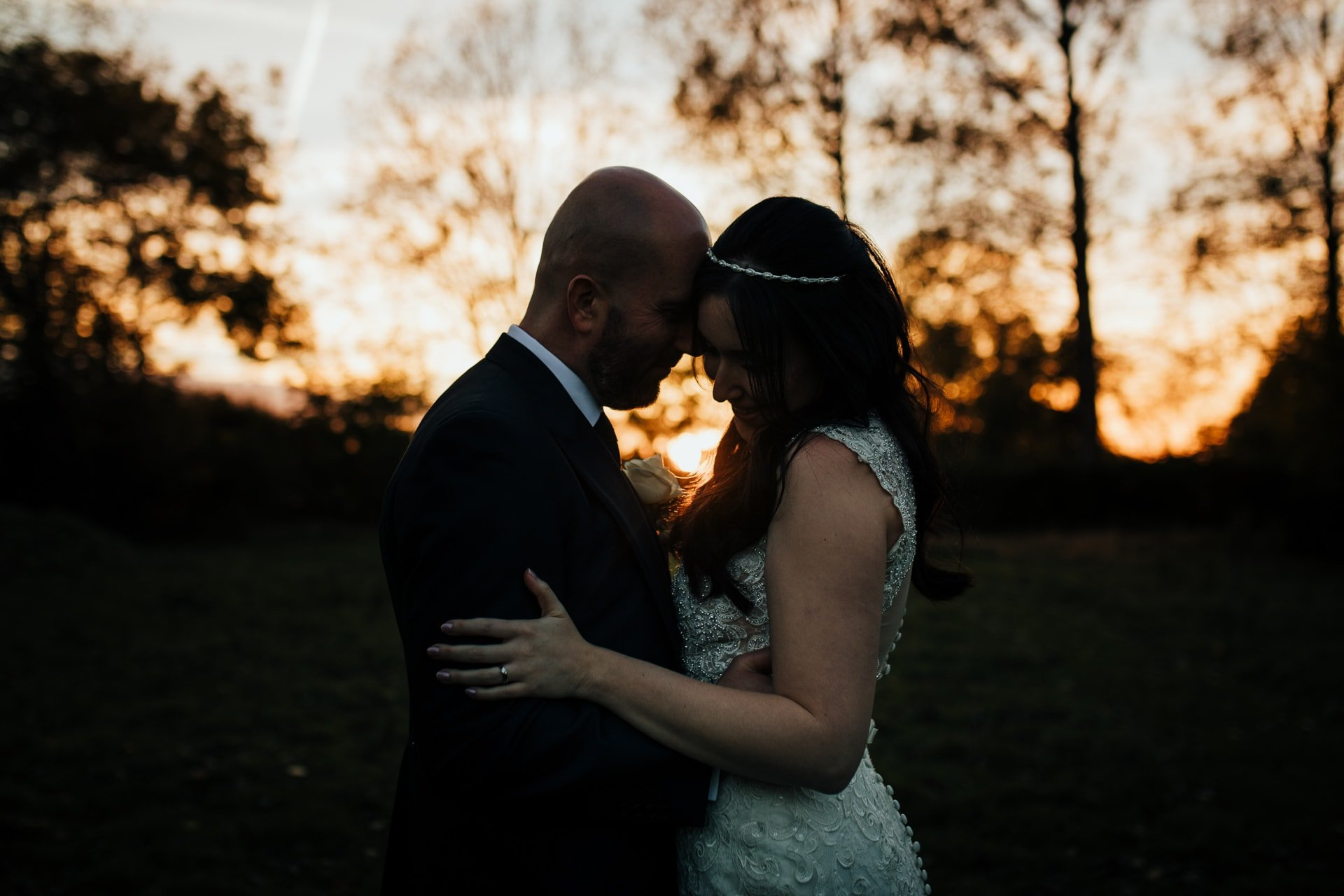 Bride and Groom holding each other as the sun sets through trees behind them