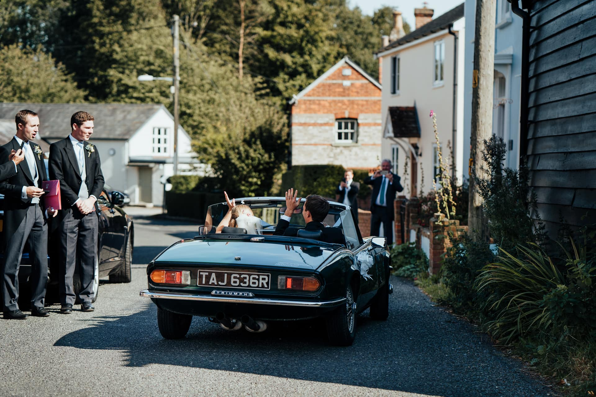 Bride and Groom wave goodbye to their guests in a vintage Triumph car