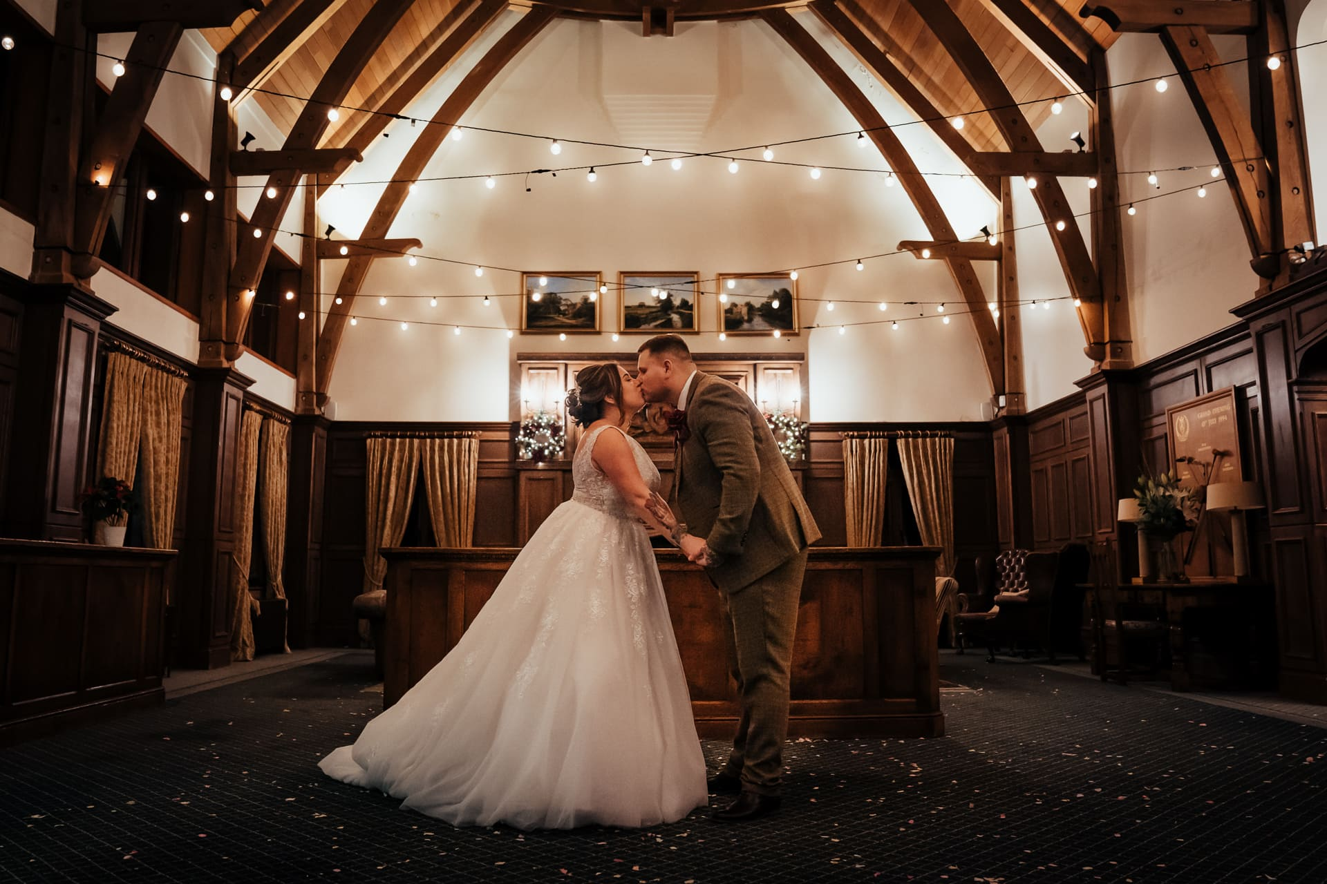 Bride and Groom kissing under the ligh s of the Great Hall at The London Golf Club