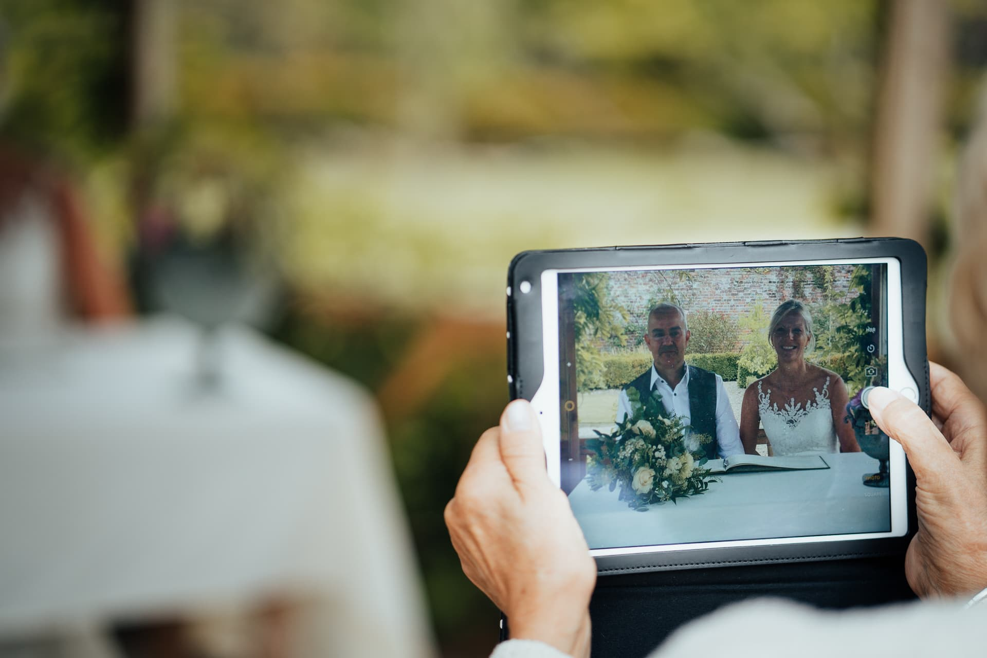 Brides mother takes pictures of Bride and Groom with her iPad
