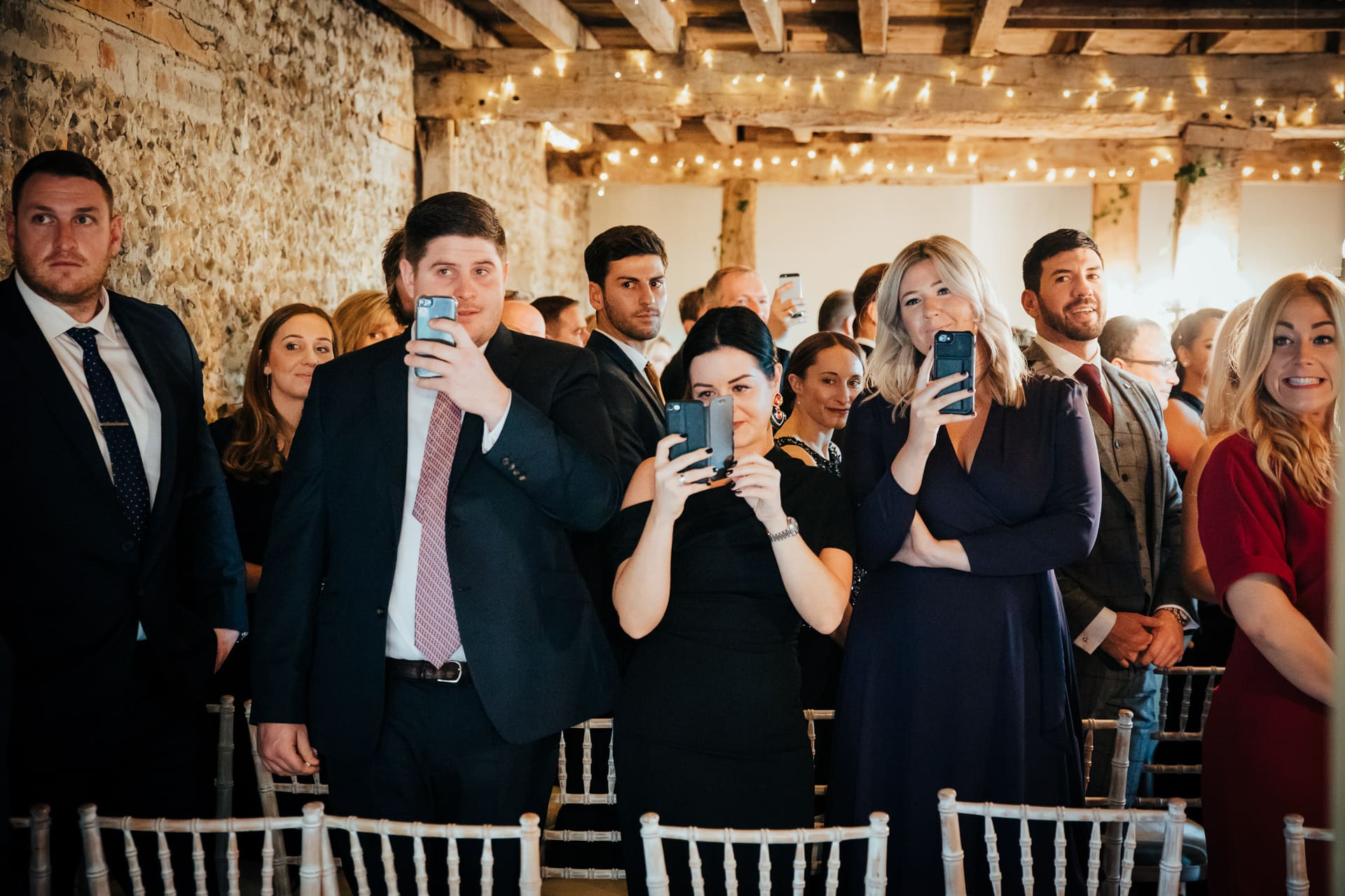Wedding guests all holding mobile phones to take pictures of the Bride as she enters