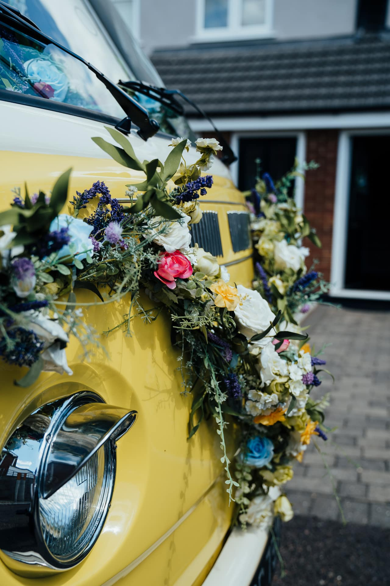 Yellow VW bus decorated with wedding flowers