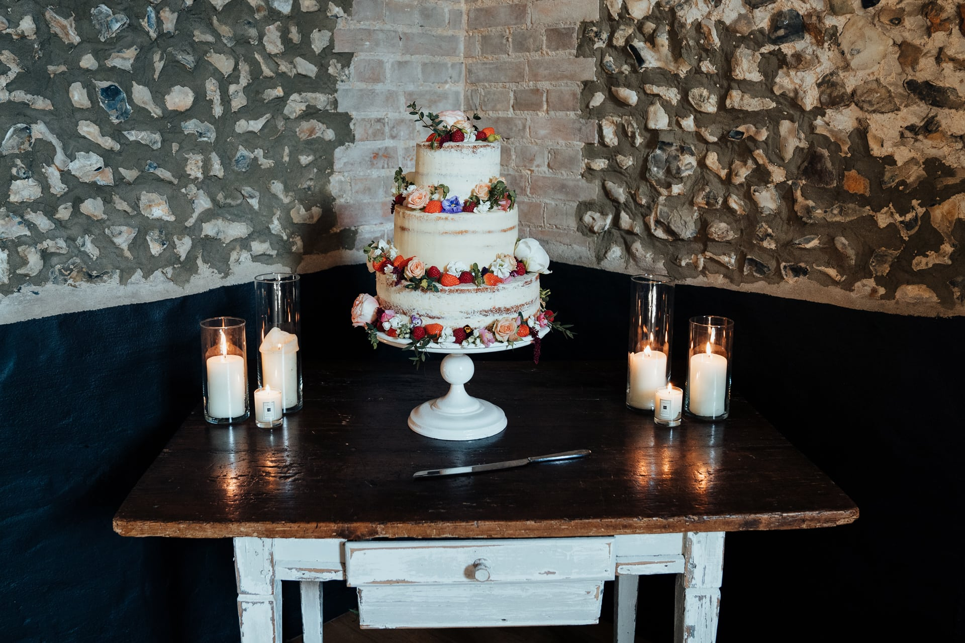 semi naked wedding cake in beautiful barn surrounding