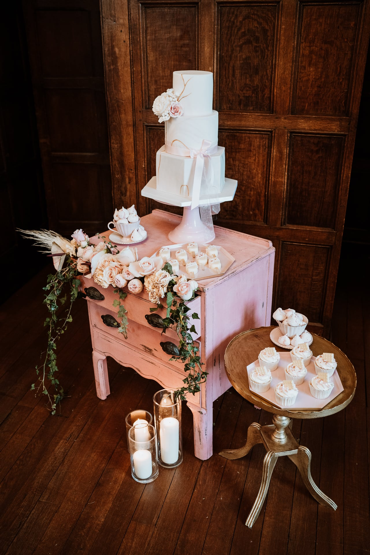 Cream marbled wedding cake and dessert table at Eastwell Manor