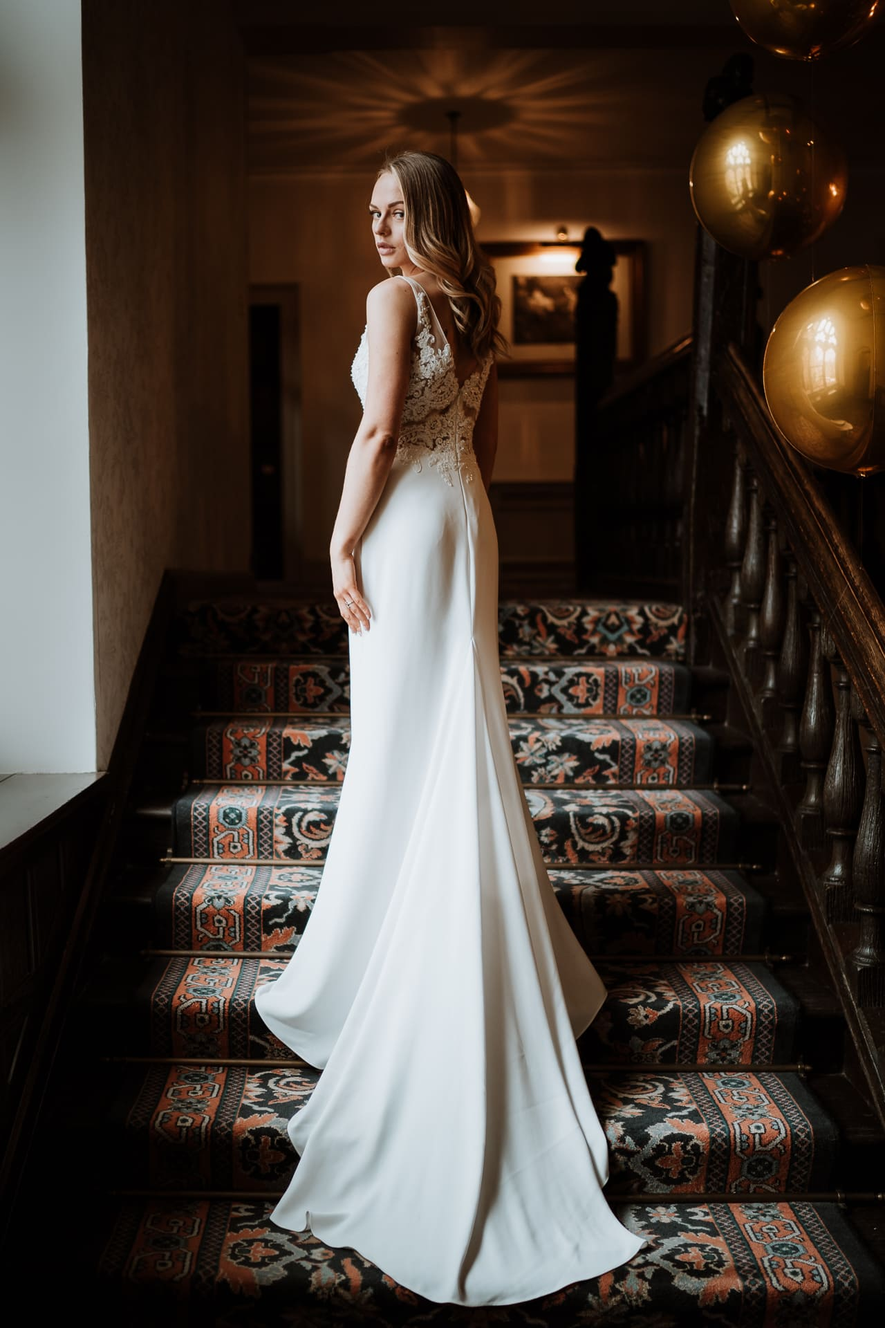 Bride on grand stairwell at Eastwell Manor