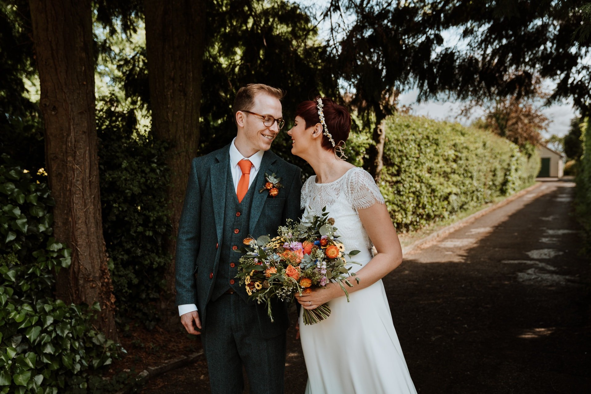 Bride and Groom with brightly coloured bouquet smiling at each other