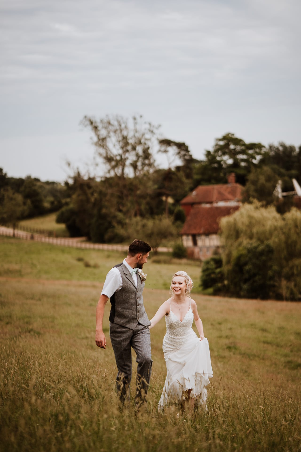 Bride smiling at her groom as they climb a hill with country side backdrop