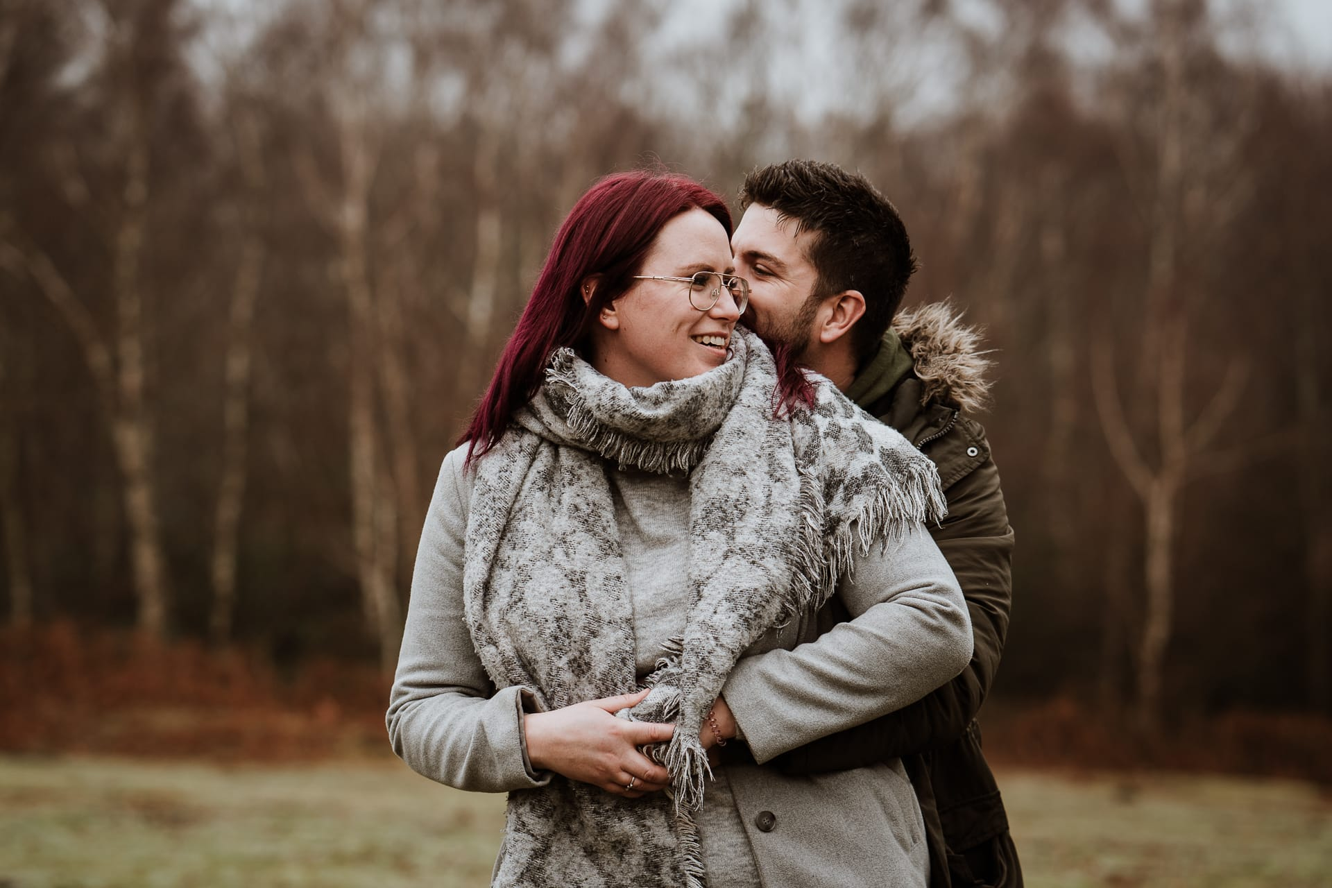 Couple embracing in woodland during their engagement shoot