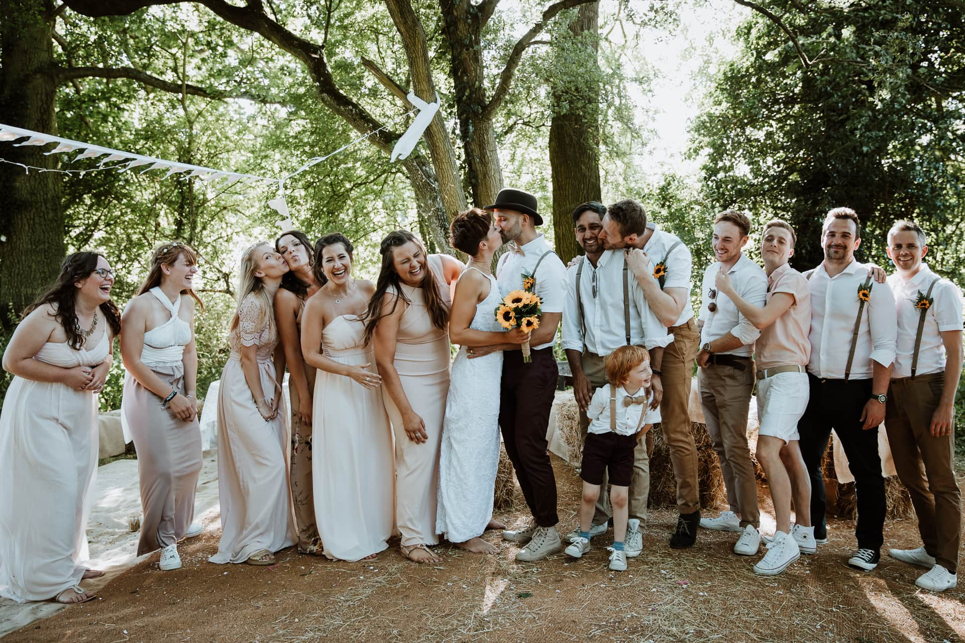 Fun wedding group shot with wedding party laughing as Bride and Groom kiss