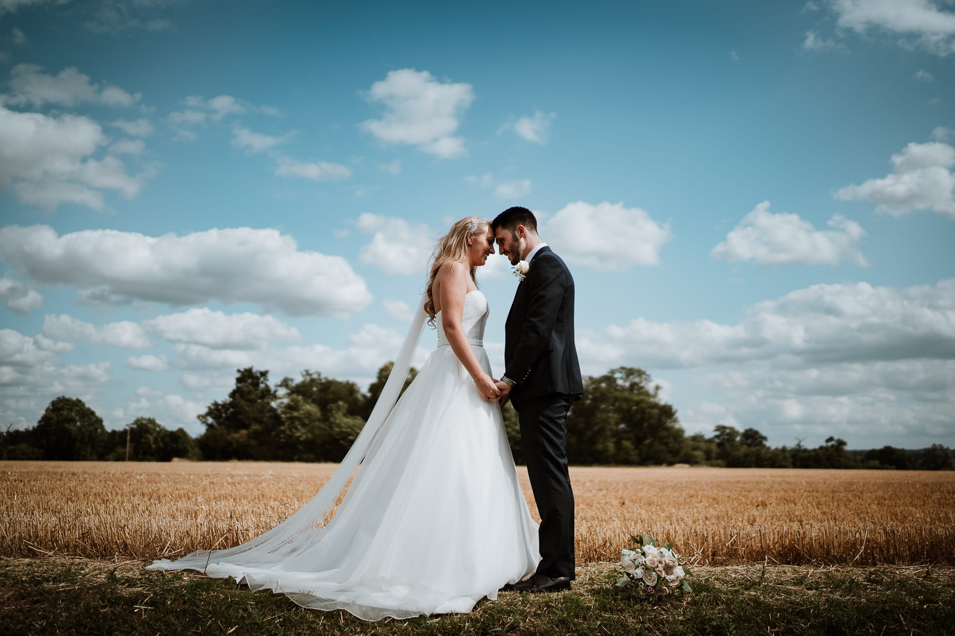Bride and groom holding hands in field under blue sky