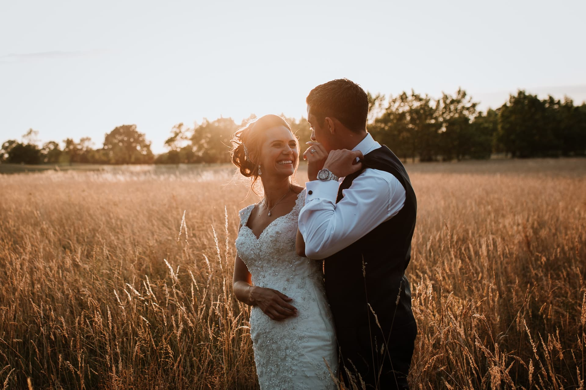 Bride and Groom looking at each other in field bathed in golden sunlight