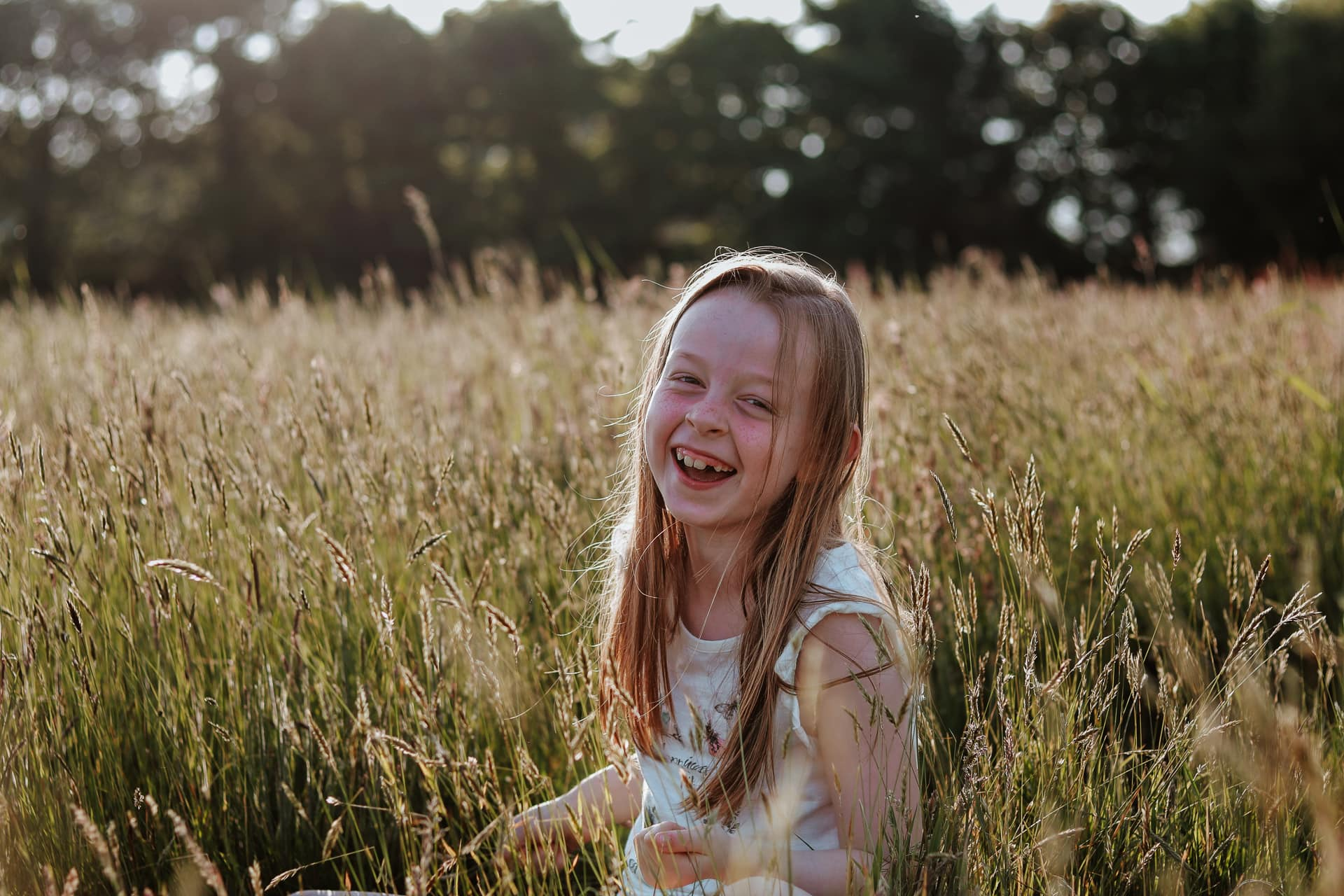 Young girl laughing in long grass in a sunny field