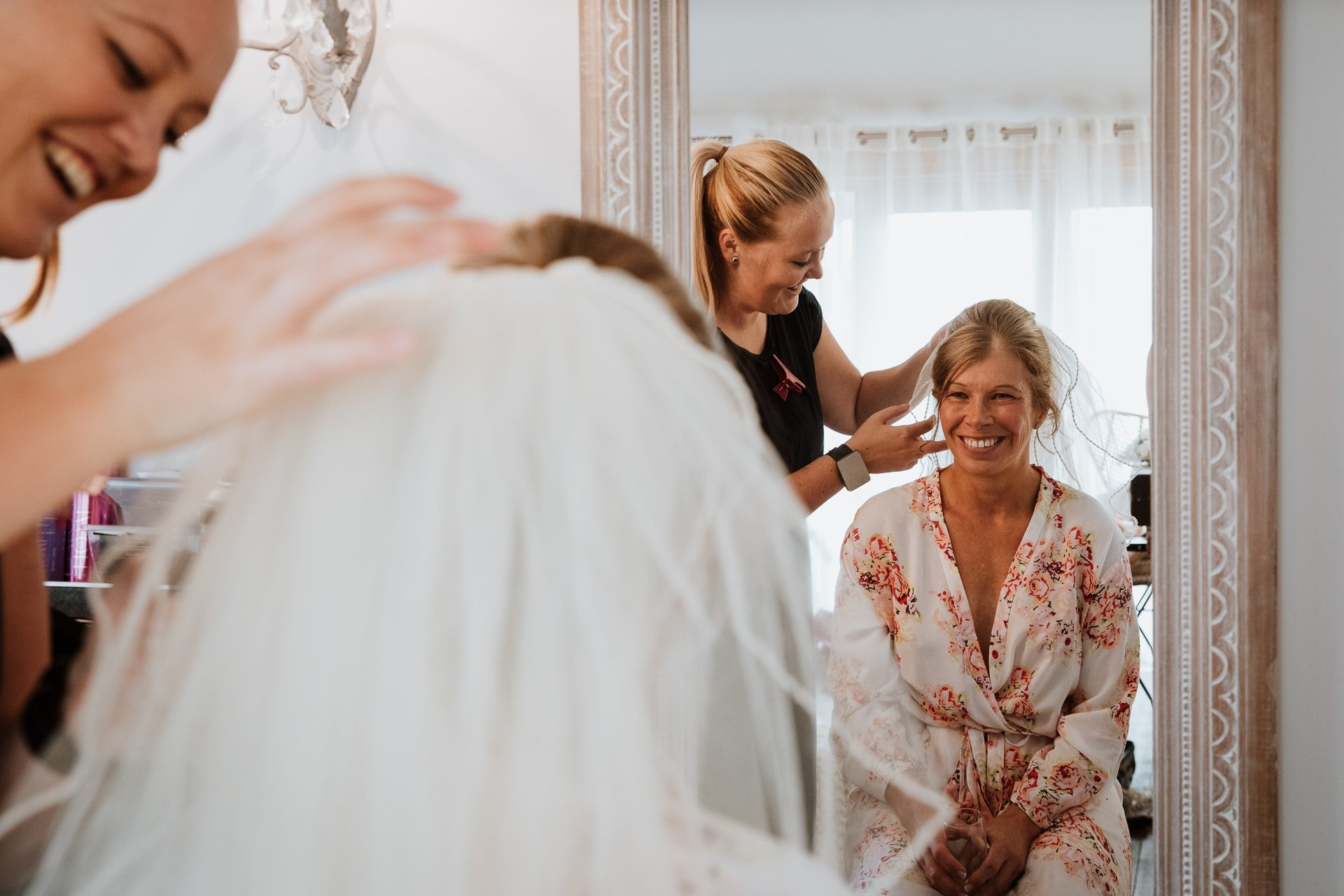 Smiling Bride looking in the mirror having her veil fitted before her wedding ceremony