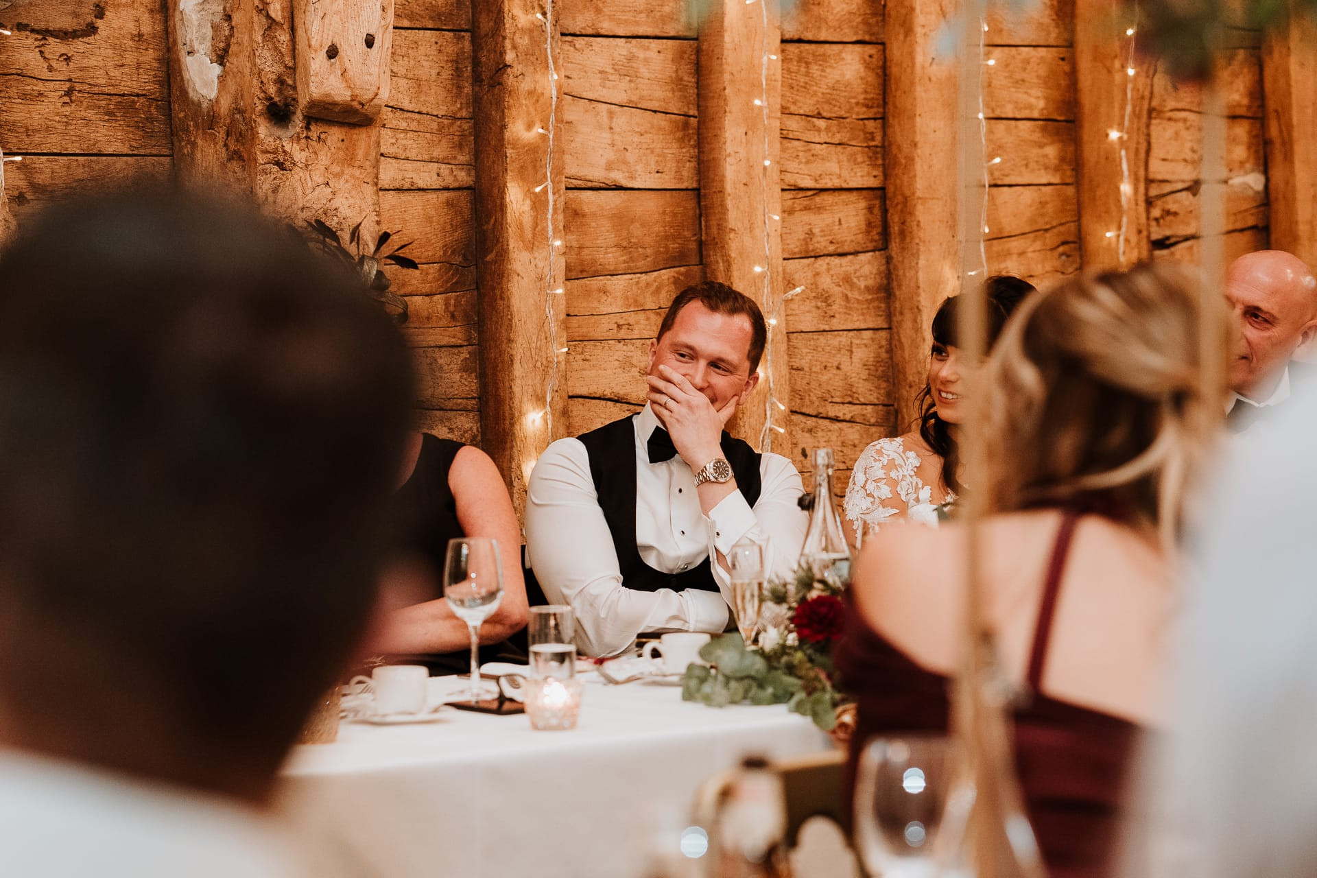 Groom hiding behind his hand during wedding speech