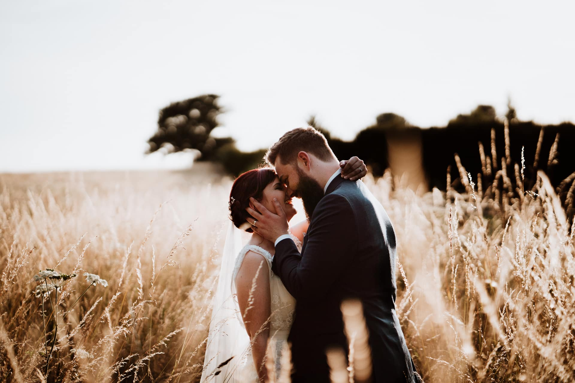 Bride and Groom node to nose and smiling in a field during sunset