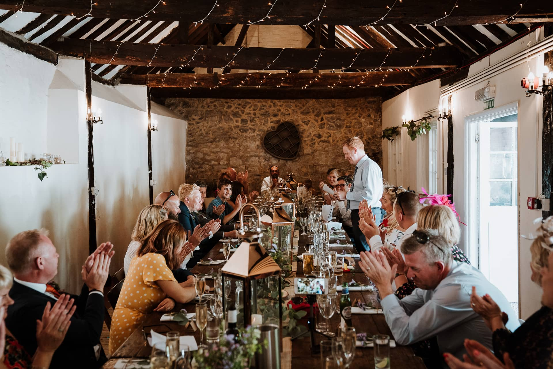 Barn wedding guests clapping during speeches