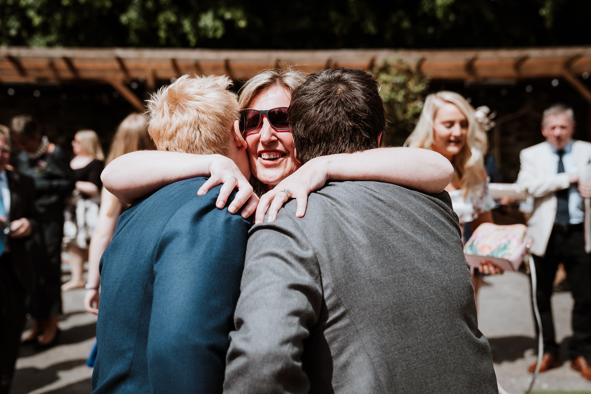 Two brides being hugged by guest after their wedding