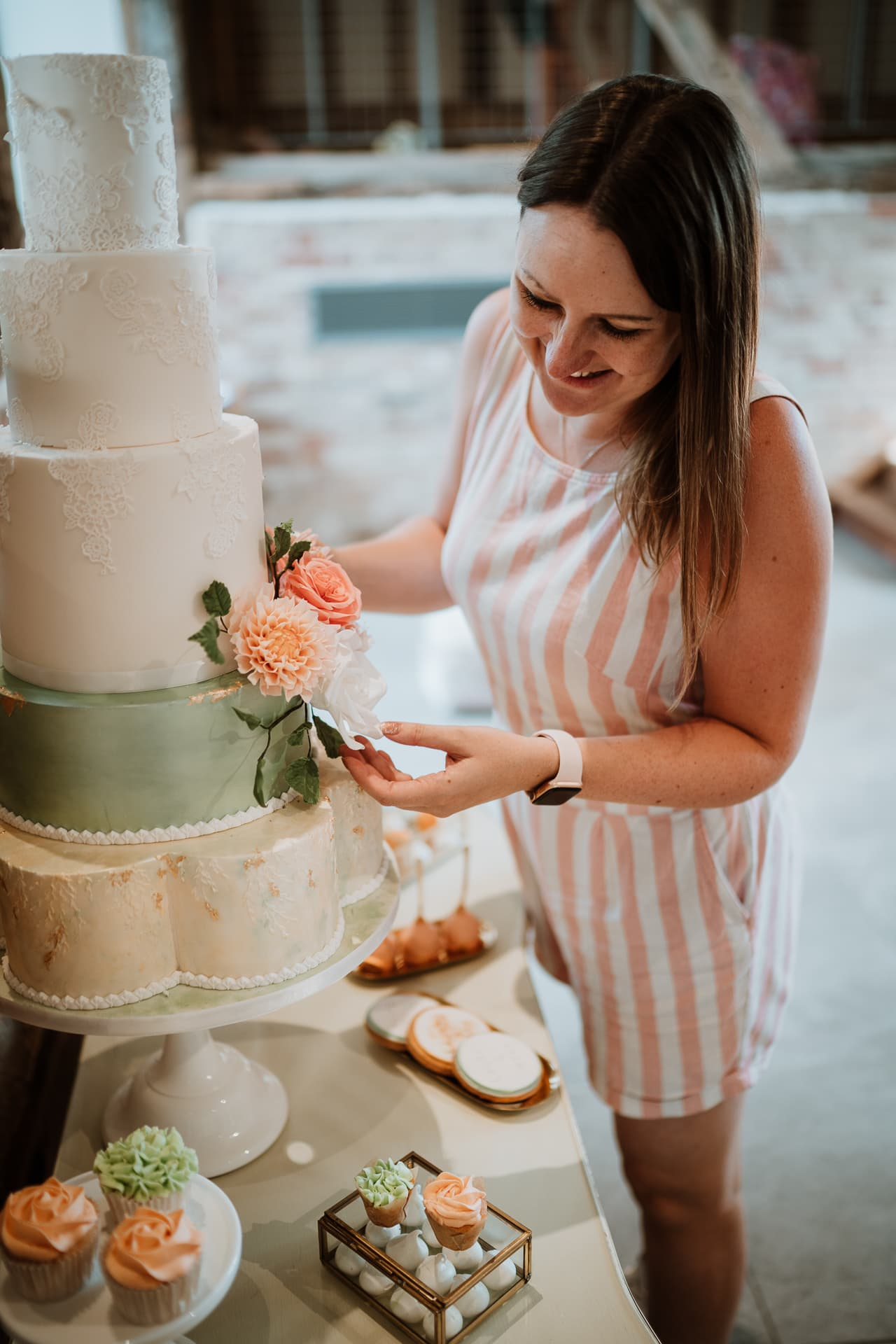 Chelsea from Chelsea Buns Cake design positioning a 5 tier wedding cake for branding portrait