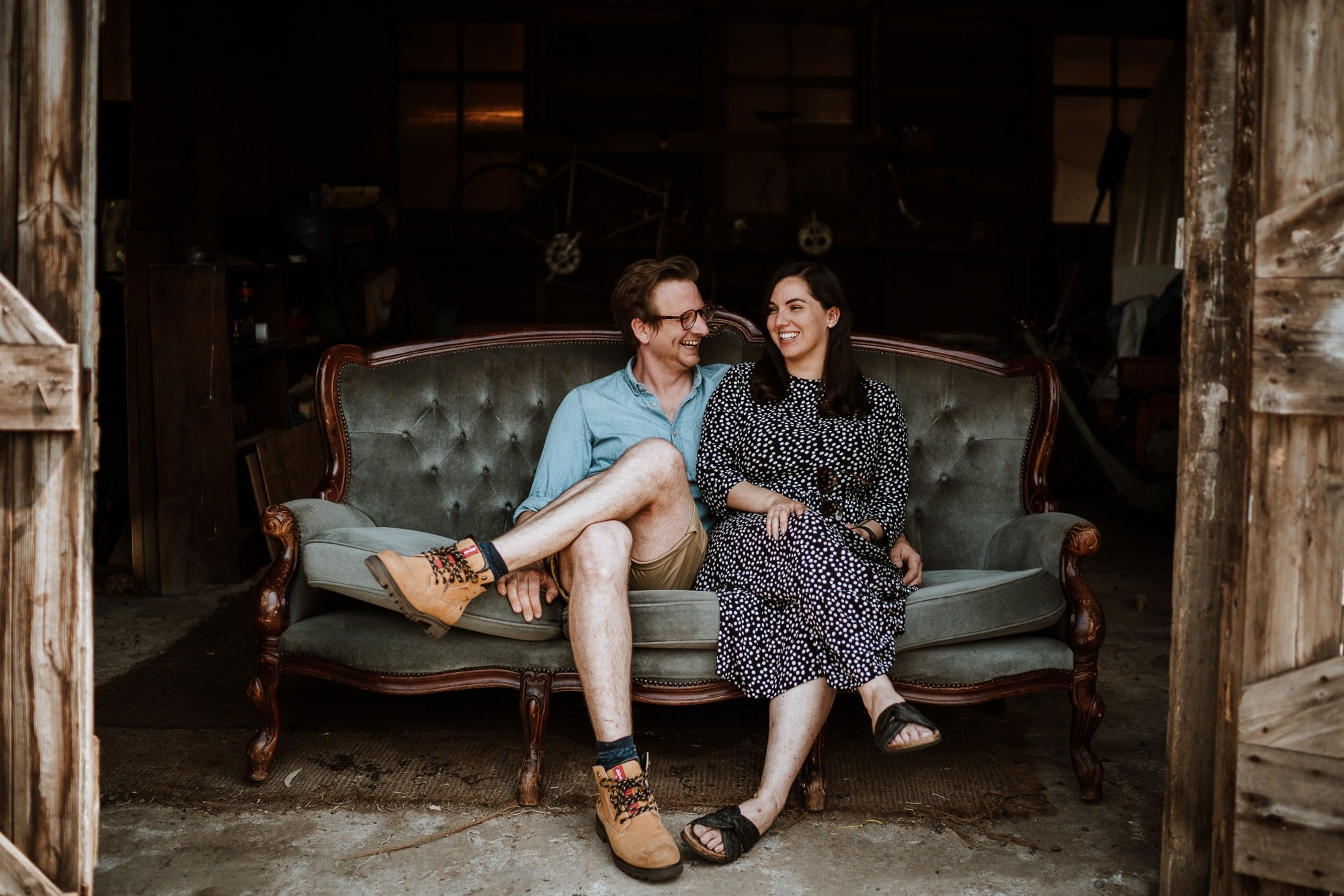 Roxanne and Ed from The Little Wedding Warehouse seated relaxed and laughing on grey sofa in rustic barn during their branding photoshoot