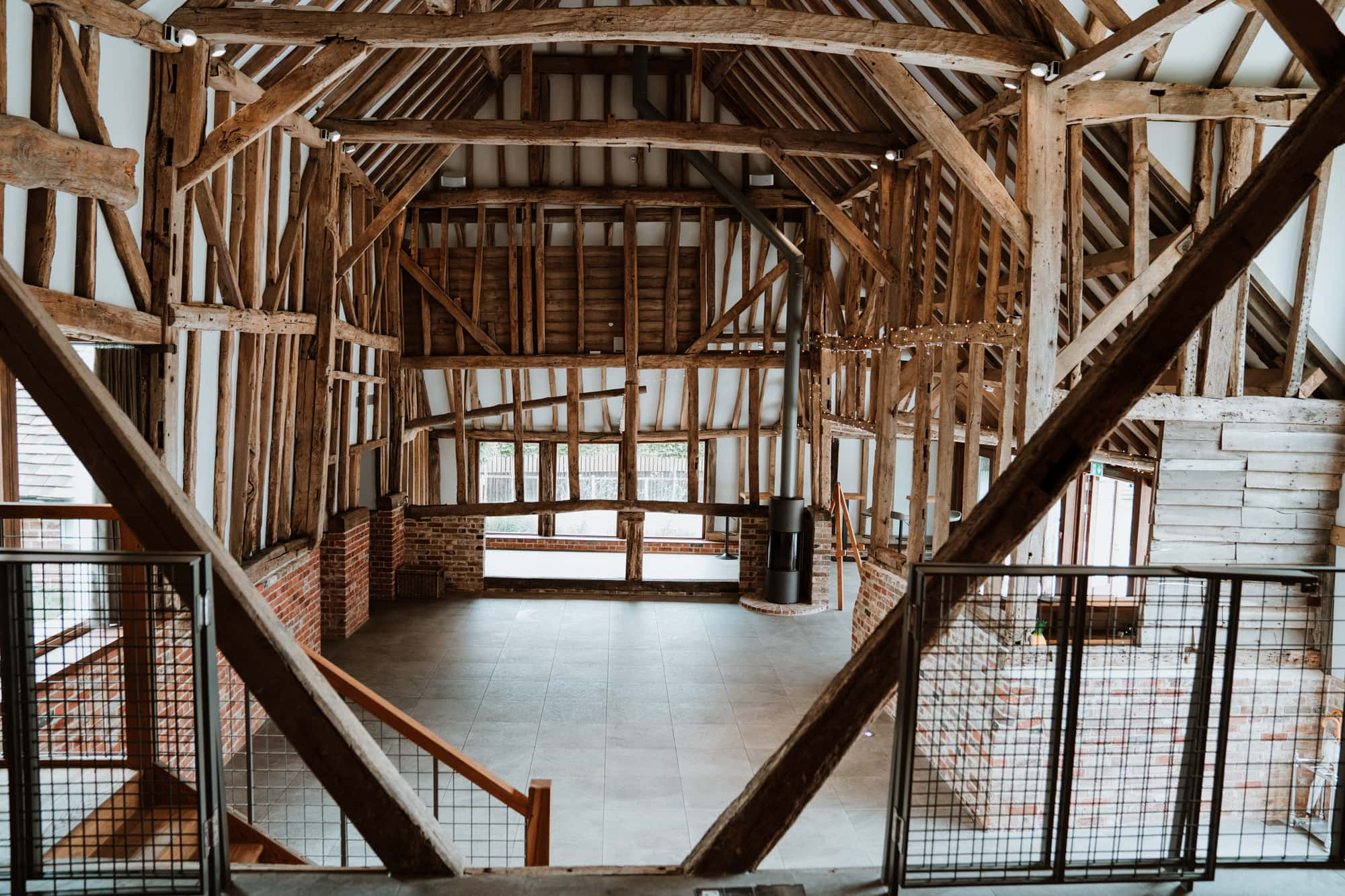 high roof and exposed beams of the interior of The Oak Barn from the raised stage