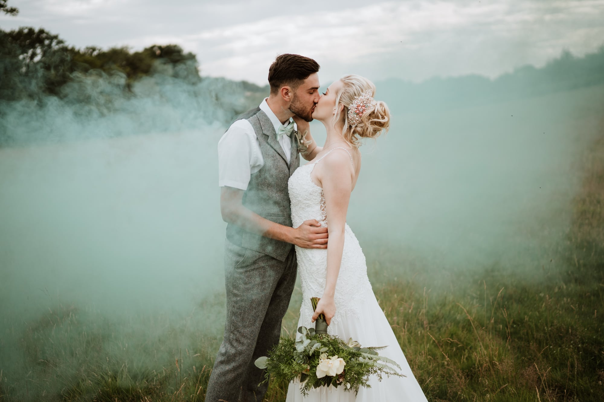 Bride and Groom kissing with a smoke bomb behind