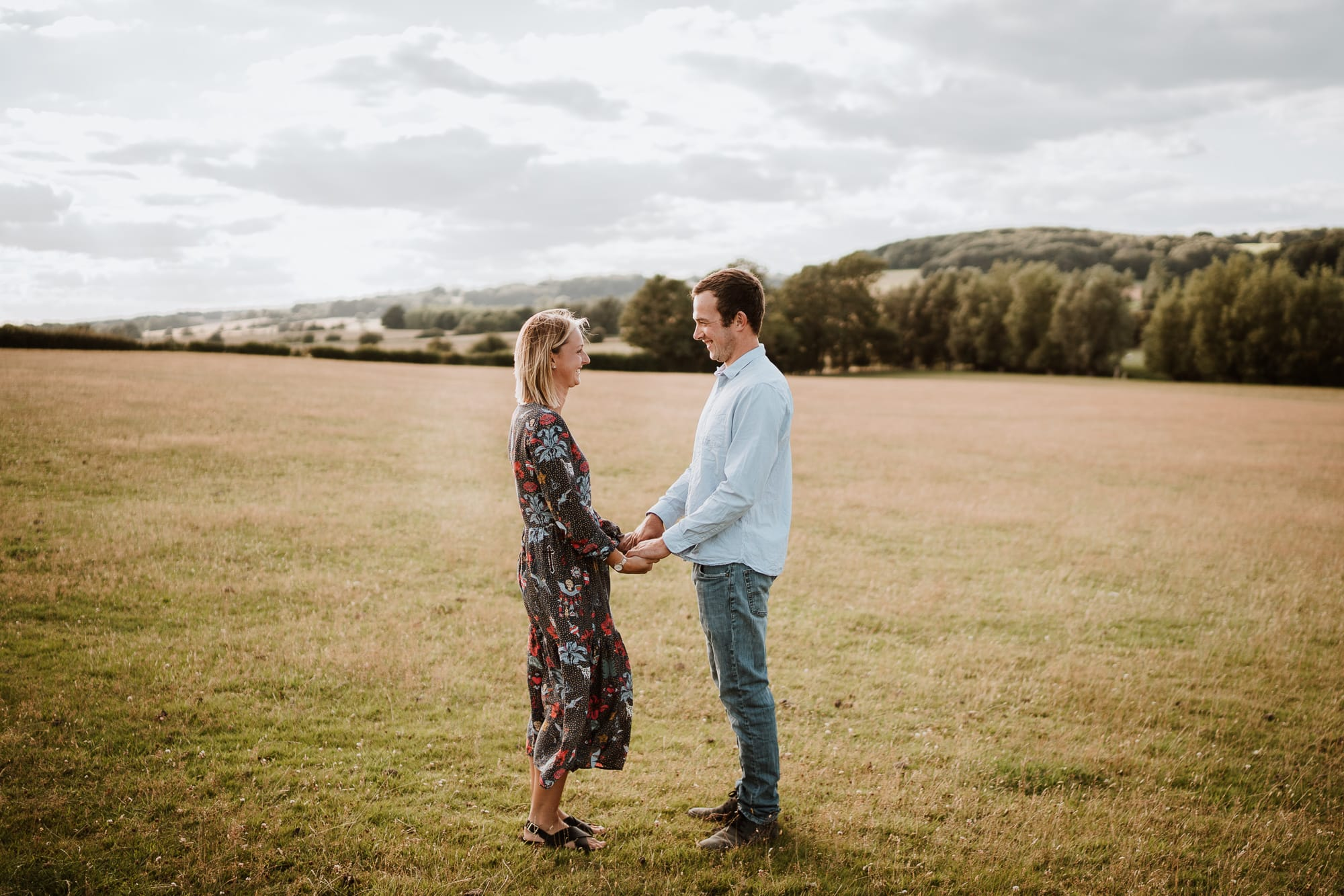 Couple holding hands and smiling in grass field in Kent