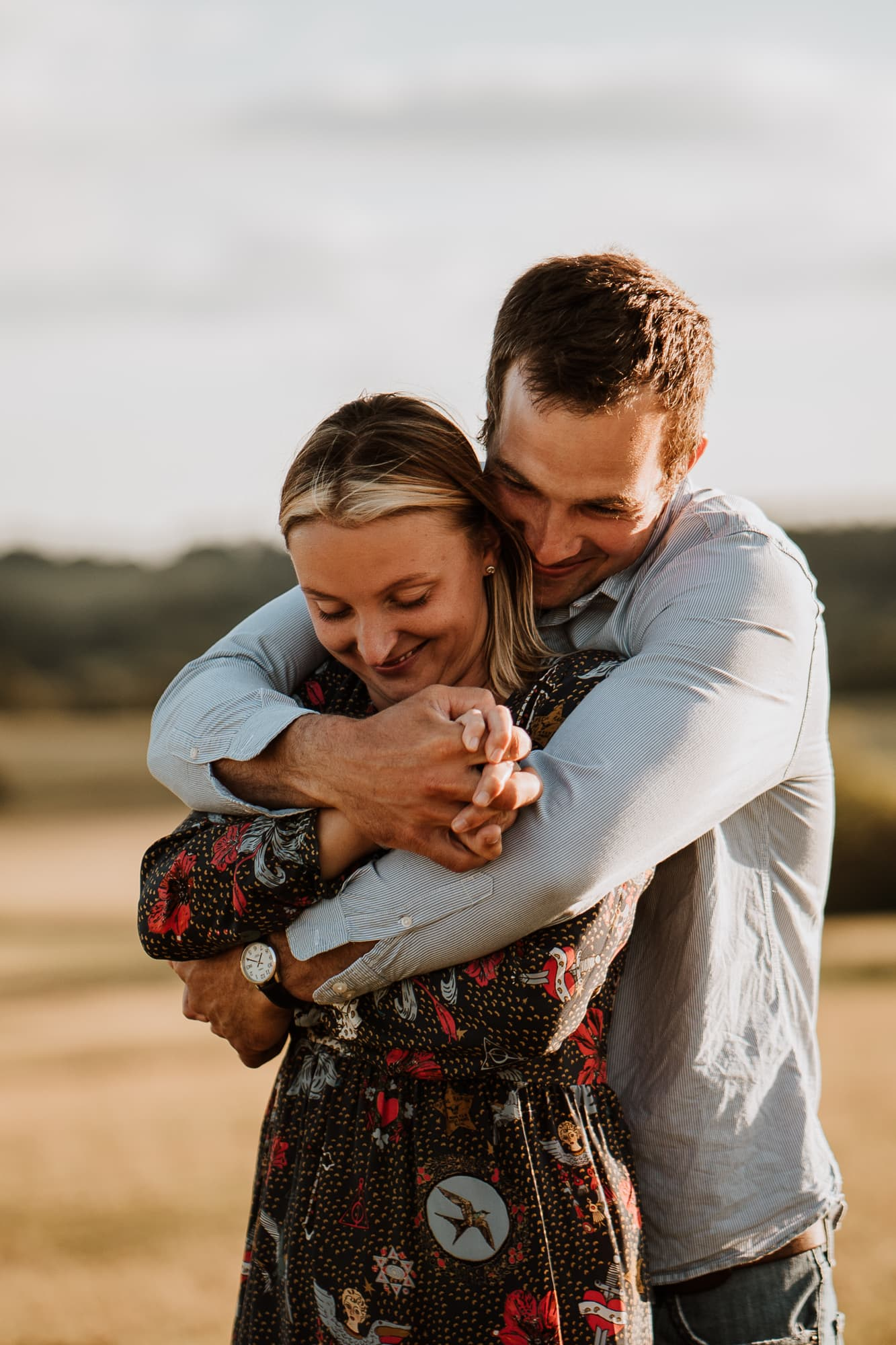 Couple with their arms wrapped around each other during their engagement photography session
