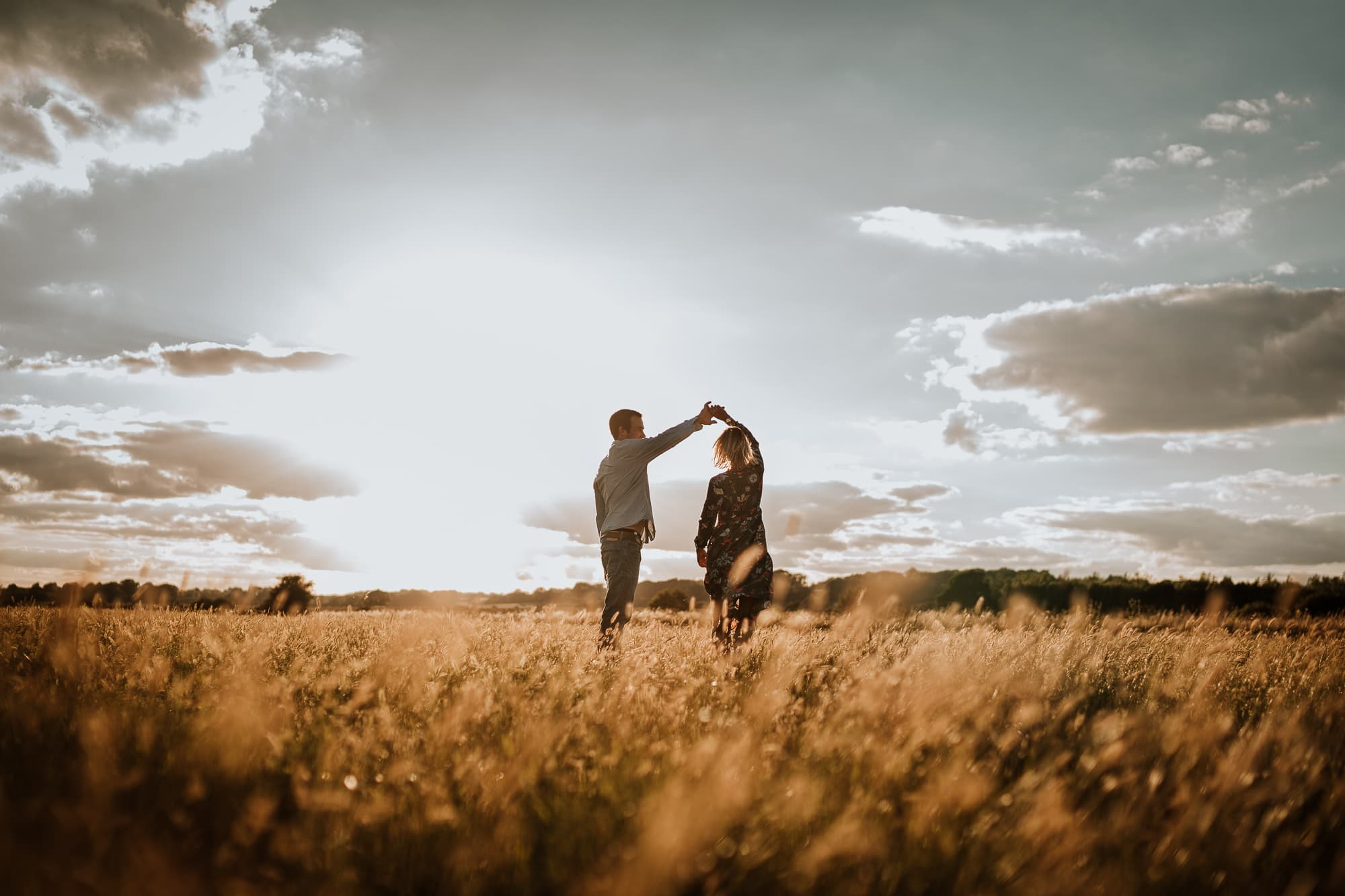 Couple dancing in long grass with the sun behind them