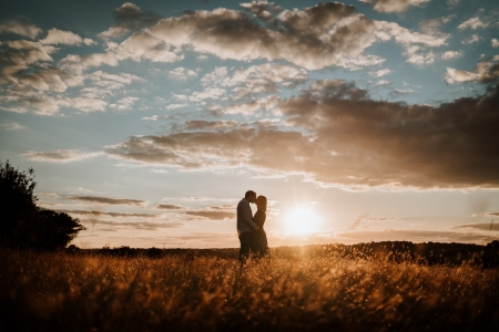 Couple kissing at golden hour in stunning sunset