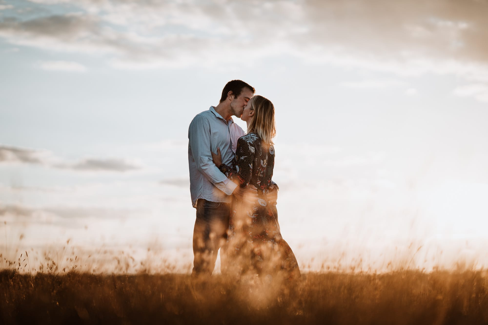 Couple kissing at sunset in long grass