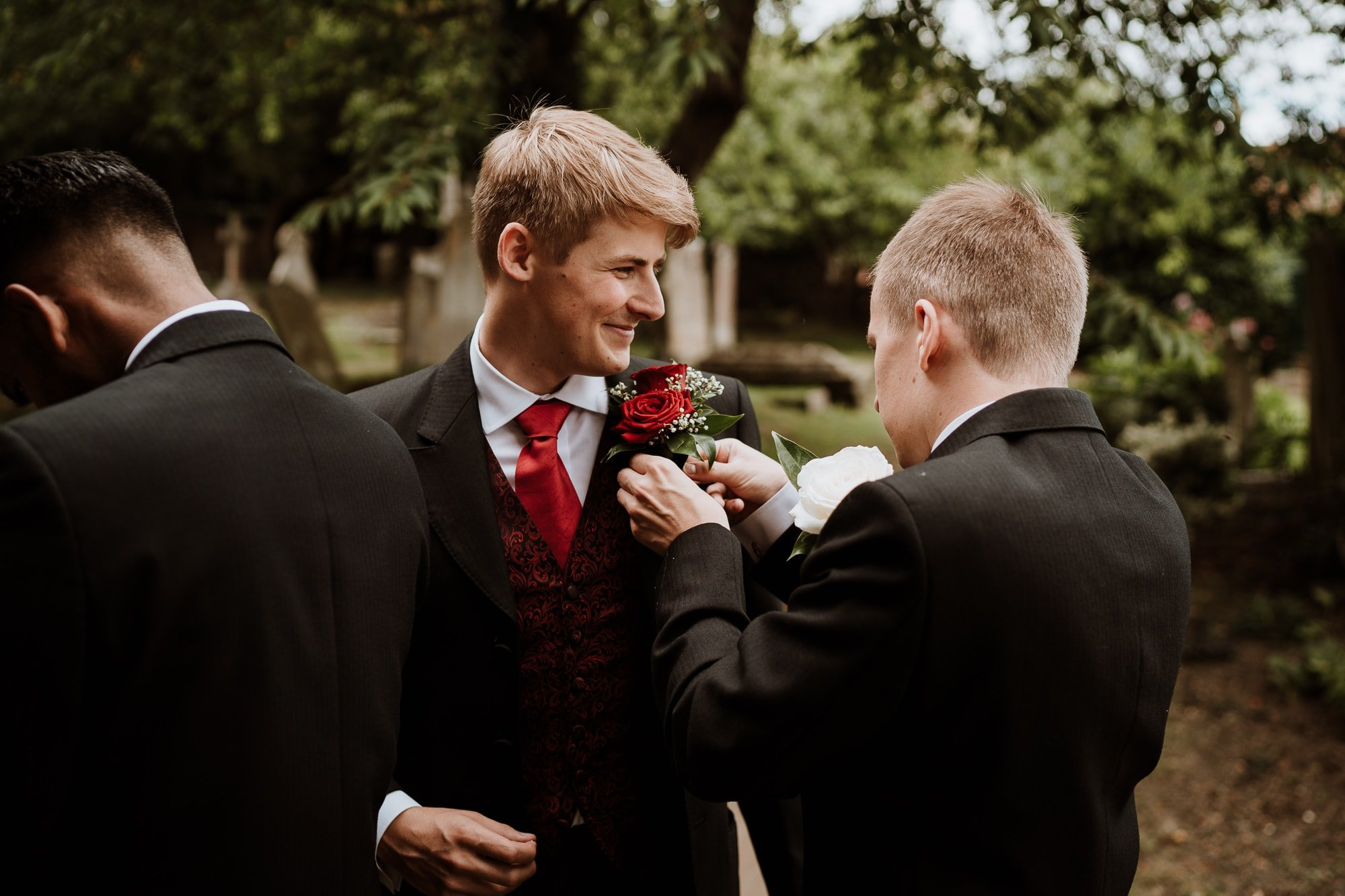 Best man applying Grooms red rose button hole before his wedding ceremony