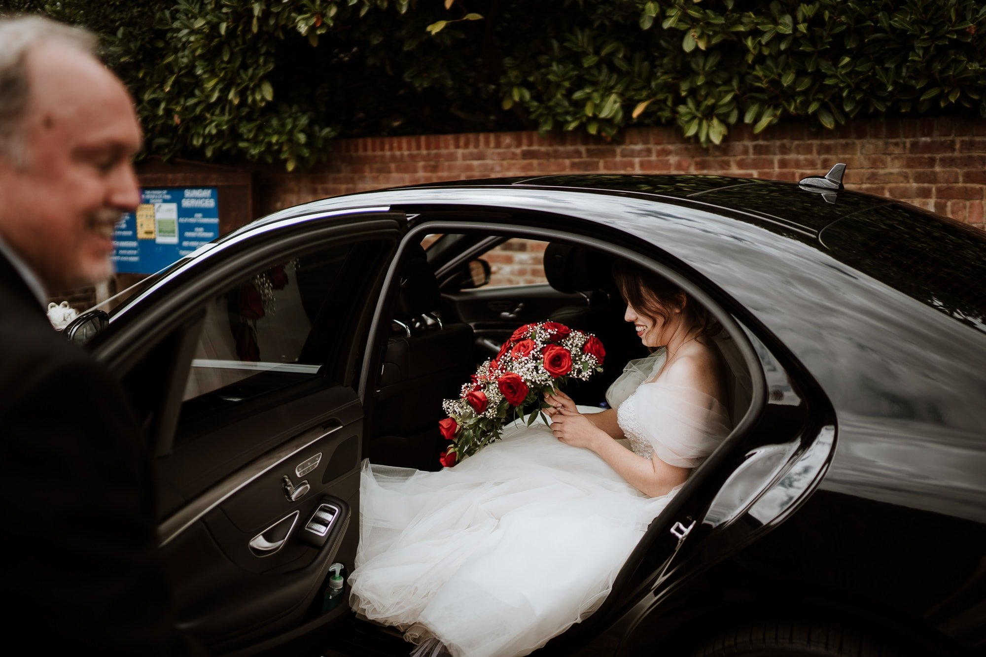 Bride arriving in the wedding car holding her red rose bouquet