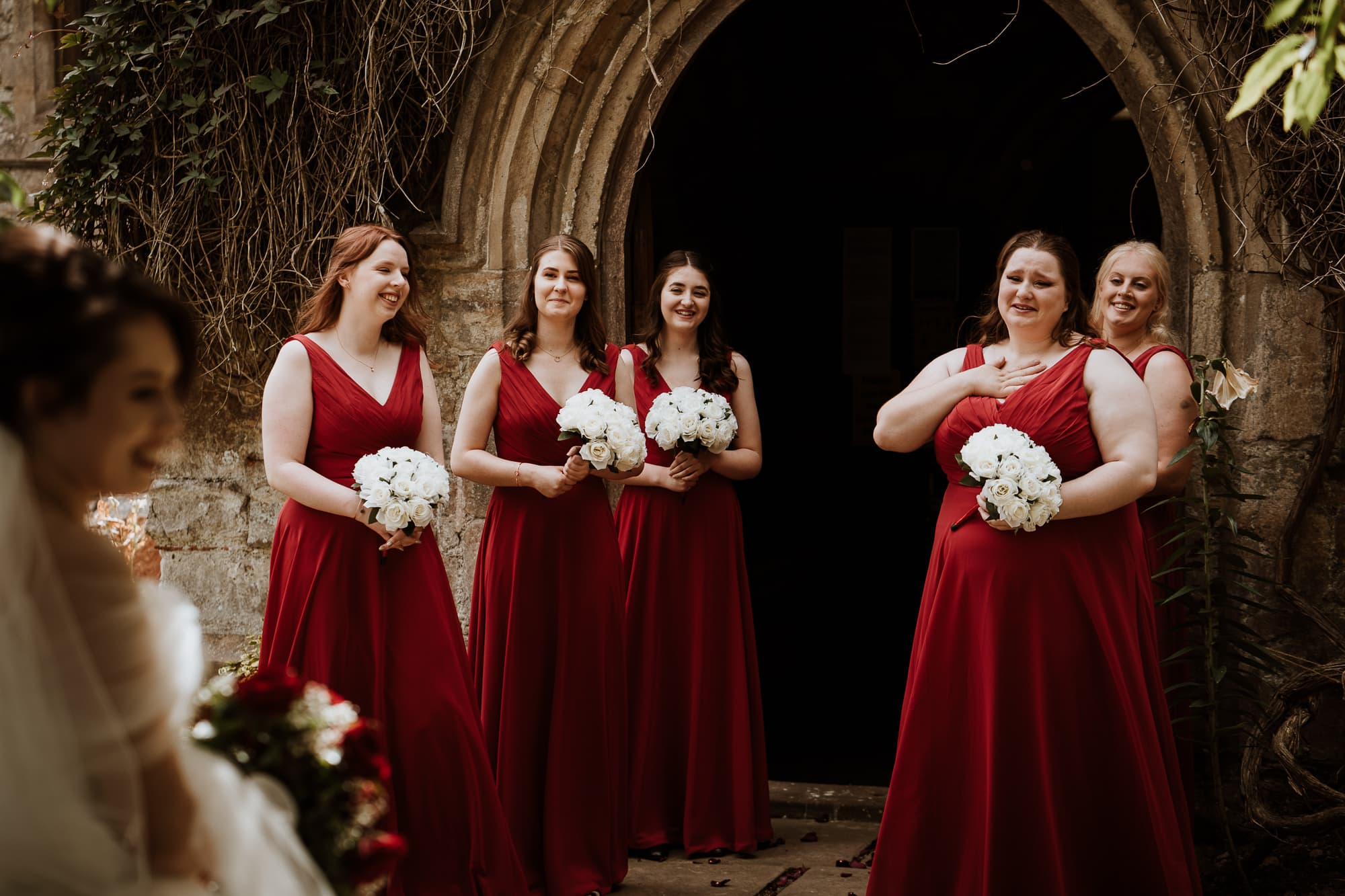 Bridesmaids dressed in dark red seeing Bride for the first time