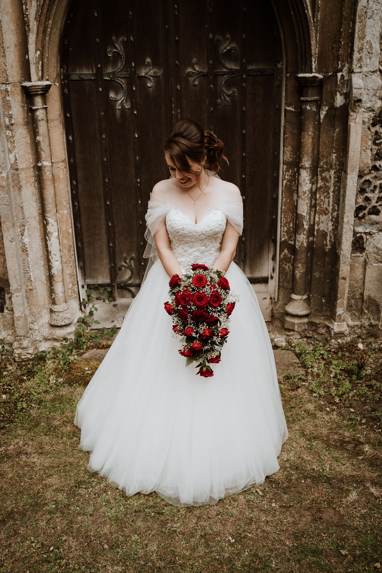 Bride holding her bouquet of red roses