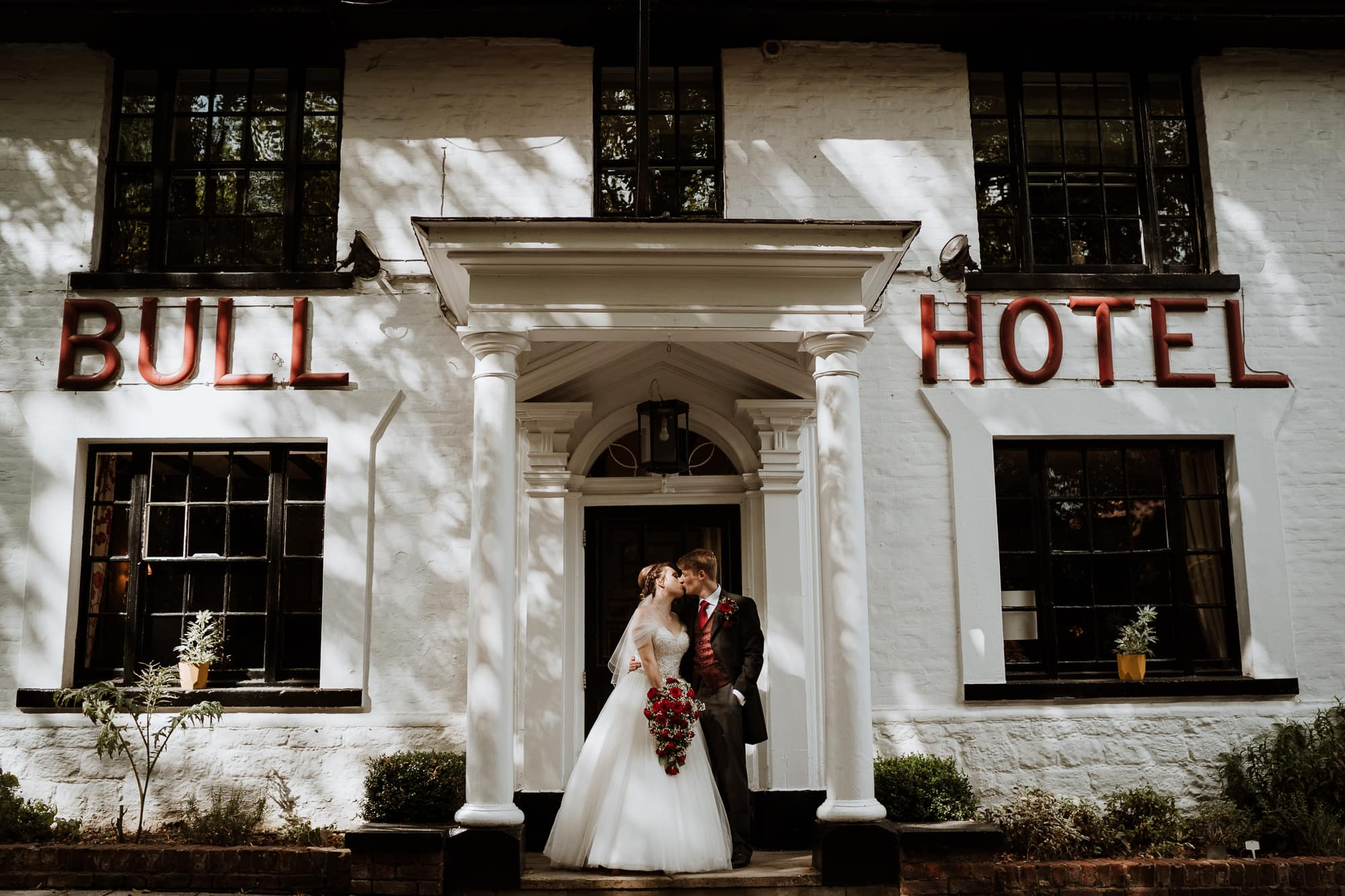 Bride and Groom kissing in the doorway of the Bull Hotel in Wrotham
