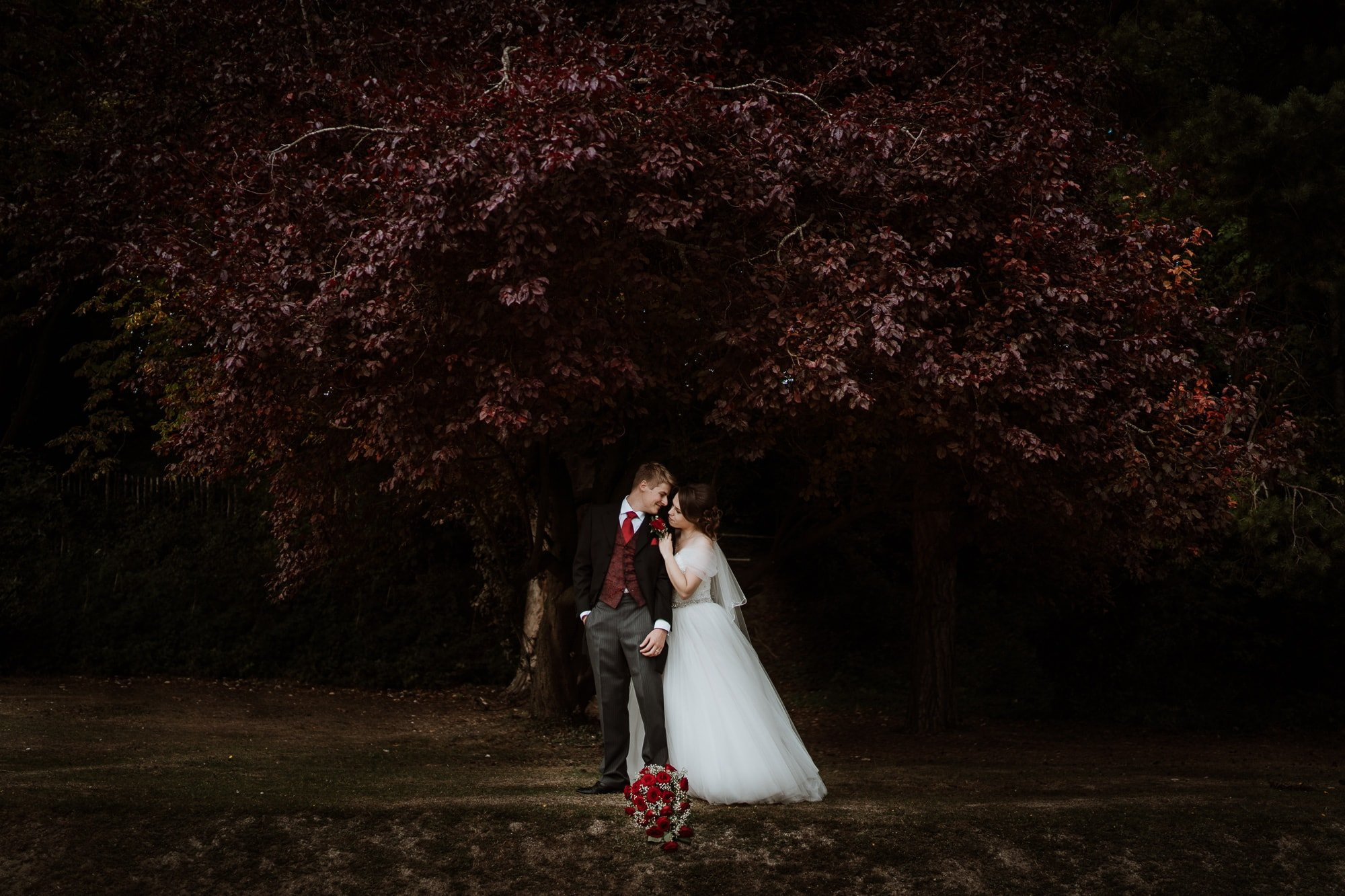 Bride leaning on Grooms shoulder under dark red tree