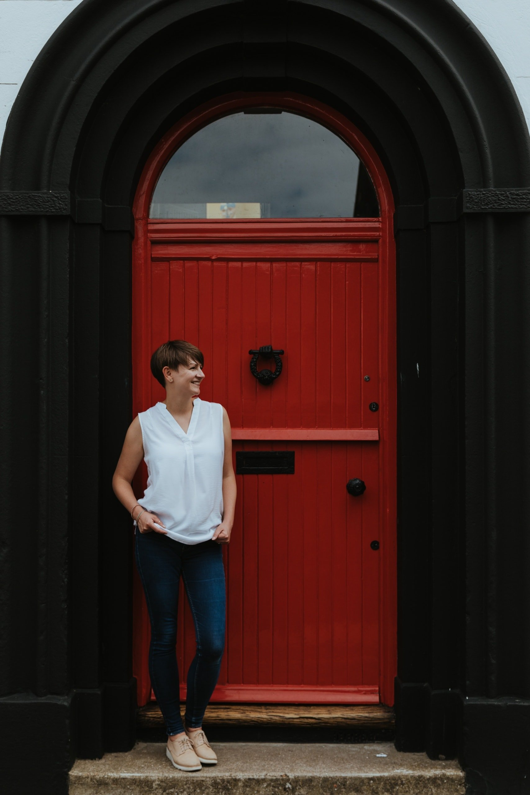 Nicola Dawson Kent Wedding Photographer smiling in front of red door