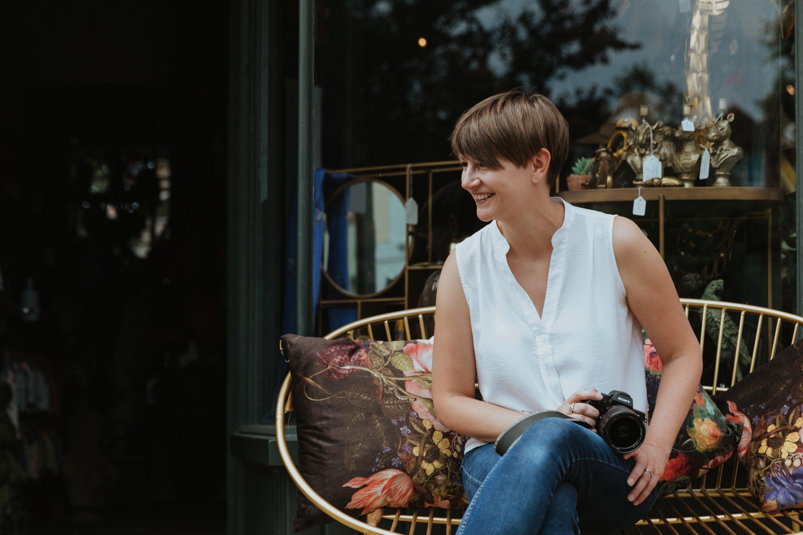 Nicola Dawson, Kent wedding photographer seated and smiling