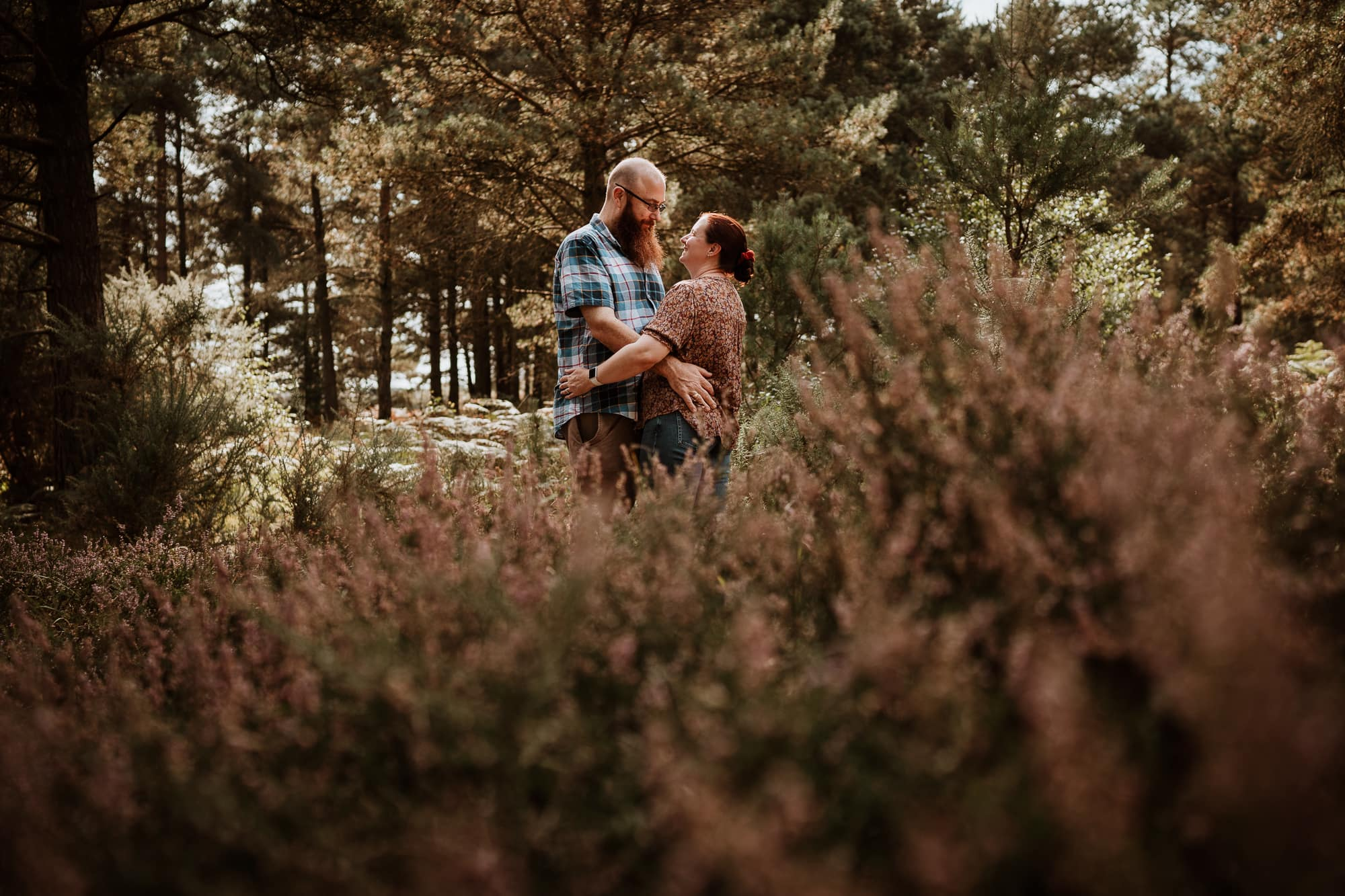Couple hugging in heather in Ashdown Forest Engagement shoot