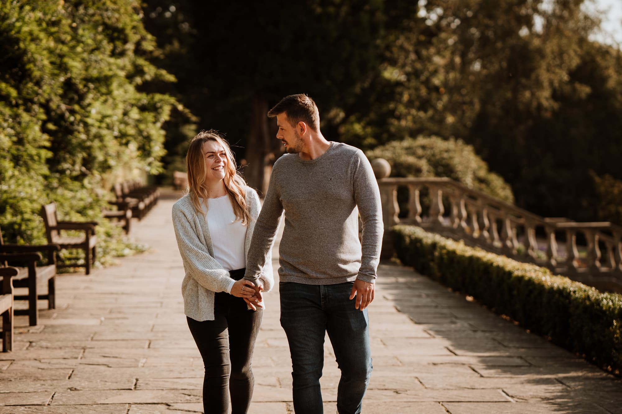 Engagemend couple walking and holding hands in park
